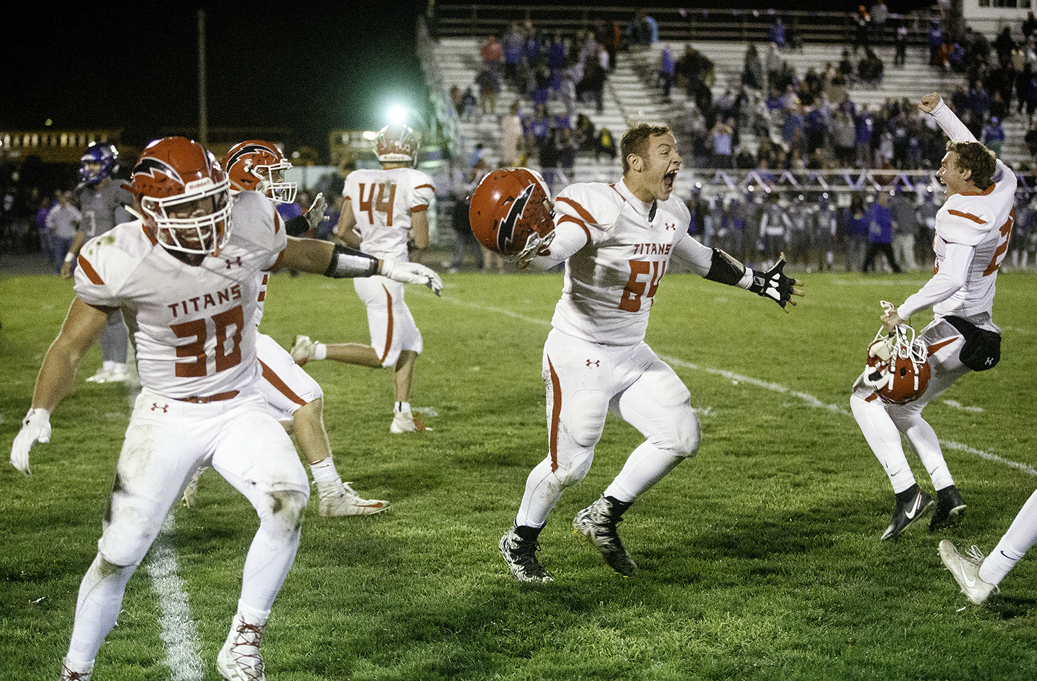 Glenwood's Sam Knepler and the Titans jump around as they celebrate their 39-32 overtime win at Decatur MacArthur High School Friday, Sept. 28, 2018. The Titans remain undefeated for the season. [Ted Schurter/The State Journal-Register]