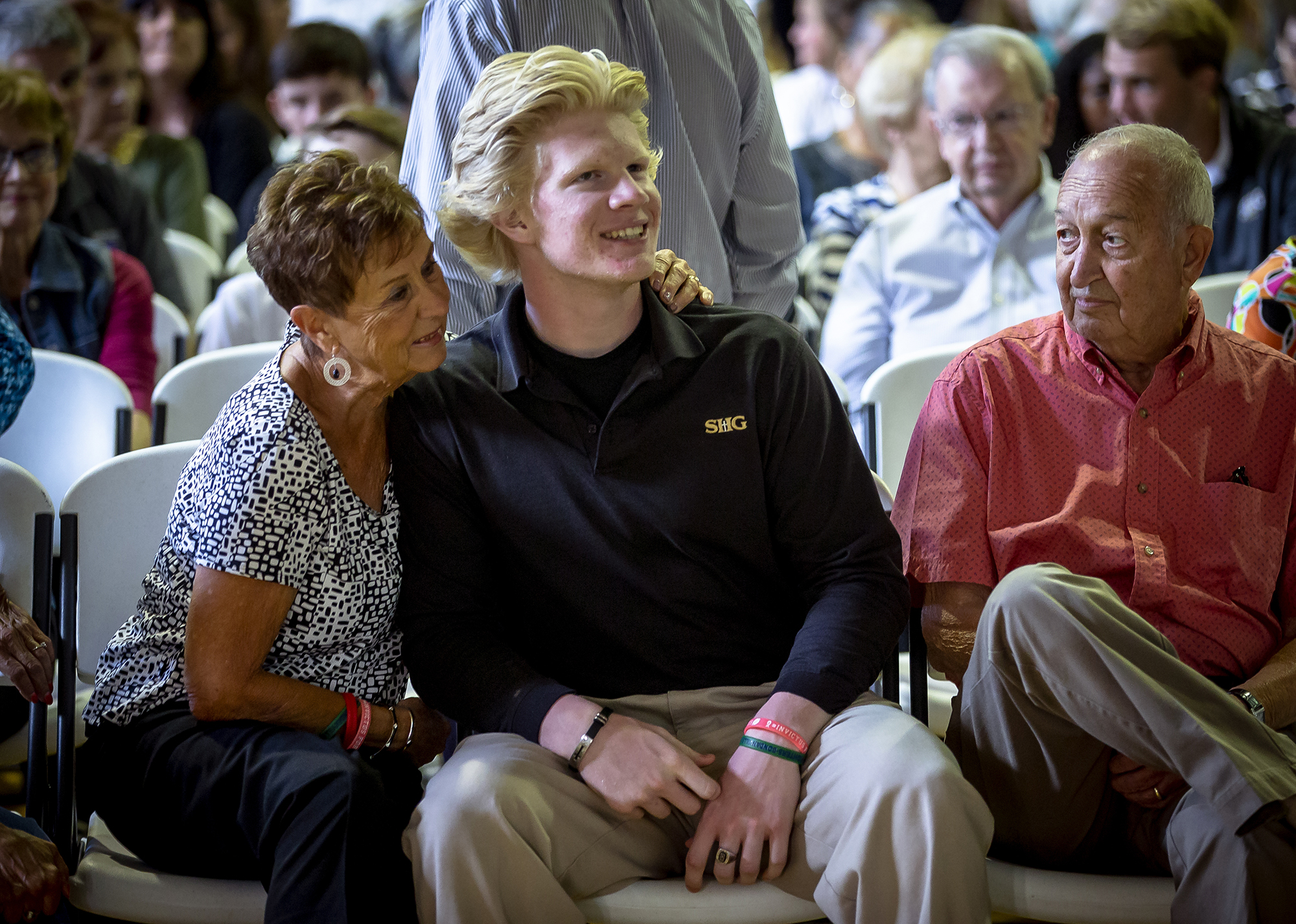 Sacred Heart-Griffins senior Michael Goldasich, center, joins his grandparents Betty Goldasich, left, and Mike Goldasich, along his with his father's godmother, Barb Kern (Not Pictured), during the first SHG Grandparent Mass inside the gymnasium at SHG's East Campus, Tuesday, Sept. 25, 2018, in Springfield, Ill. Over 250 grandparents joined with their SHG students for an all school mass followed by cookies that were baked by the cafeteria staff. [Justin L. Fowler/The State Journal-Register]