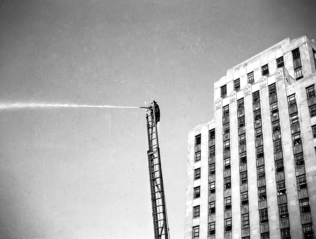 Fire fighter on ladder truck with hose, Springfield Fire Department conducts fire prevention demonstration downtown Springfield, October 10, 1941. [File/The State Journal-Register]