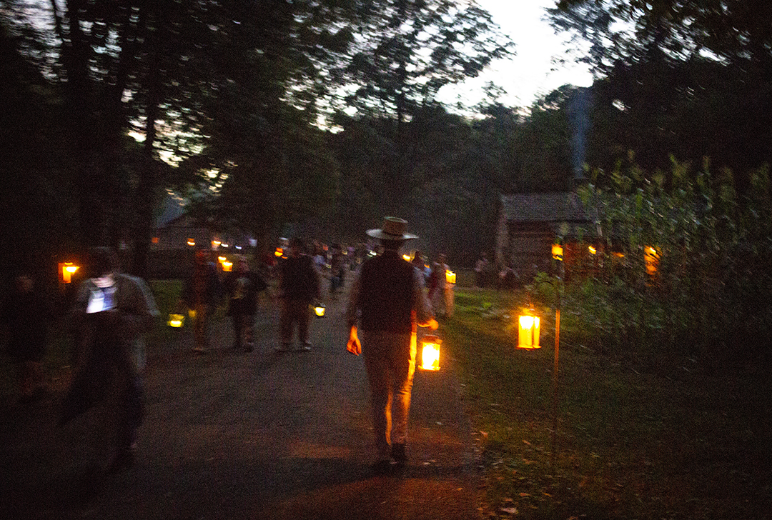 Michael Shereda carries a candlelight lantern through the dwindling daylight at the annual candlelight walk in Lincoln's New Salem State Historic Site Friday, Oct. 5, 2018, in Petersburg, Ill. [Rich Saal/The State Journal-Register]