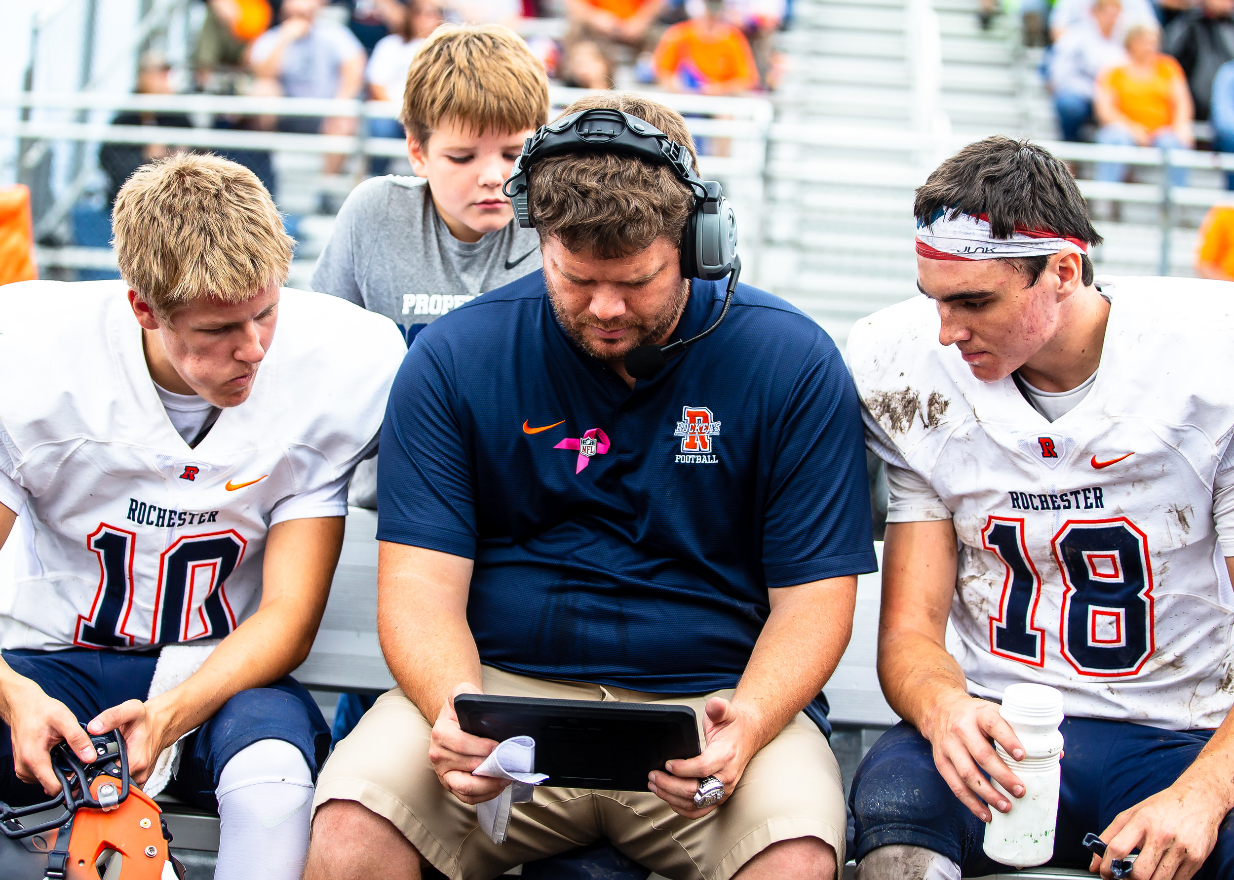 Rochester head coach Derek Leonard goes over replays with quarterbacks Brock Mackiney (10) and Clay Bruno (18)  as his son, Blake, watches over his shoulder as the Rockets take on Springfield at Memorial Stadium, Saturday, Oct. 6, 2018, in Springfield, Ill. [Justin L. Fowler/The State Journal-Register]