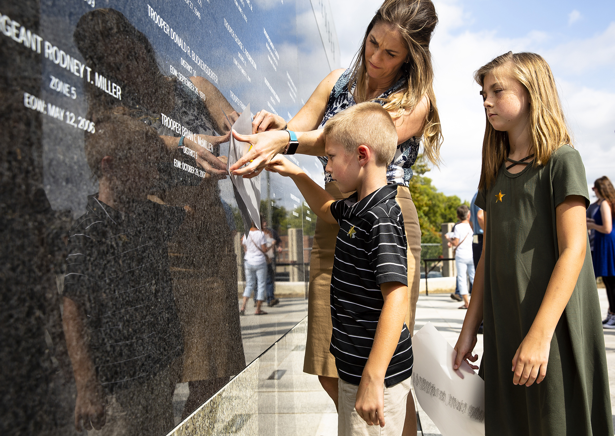 Sarah Deatherage-Steele, the widow of Trooper Kyle Deatherage, and her children, Camden, 6, and Kaylee, 10, create a rubbing of her late husband's name that is etched on a memorial wall at the Illinois State Police Memorial Park following a dedication ceremony Tuesday, Oct. 2, 2018 at 615 W. Lawrence in Springfield, Ill. Deatherage was struck and killed by a truck while makng a traffic stop in 2012 on Interstate 55 near Litchfield. [Rich Saal/The State Journal-Register]