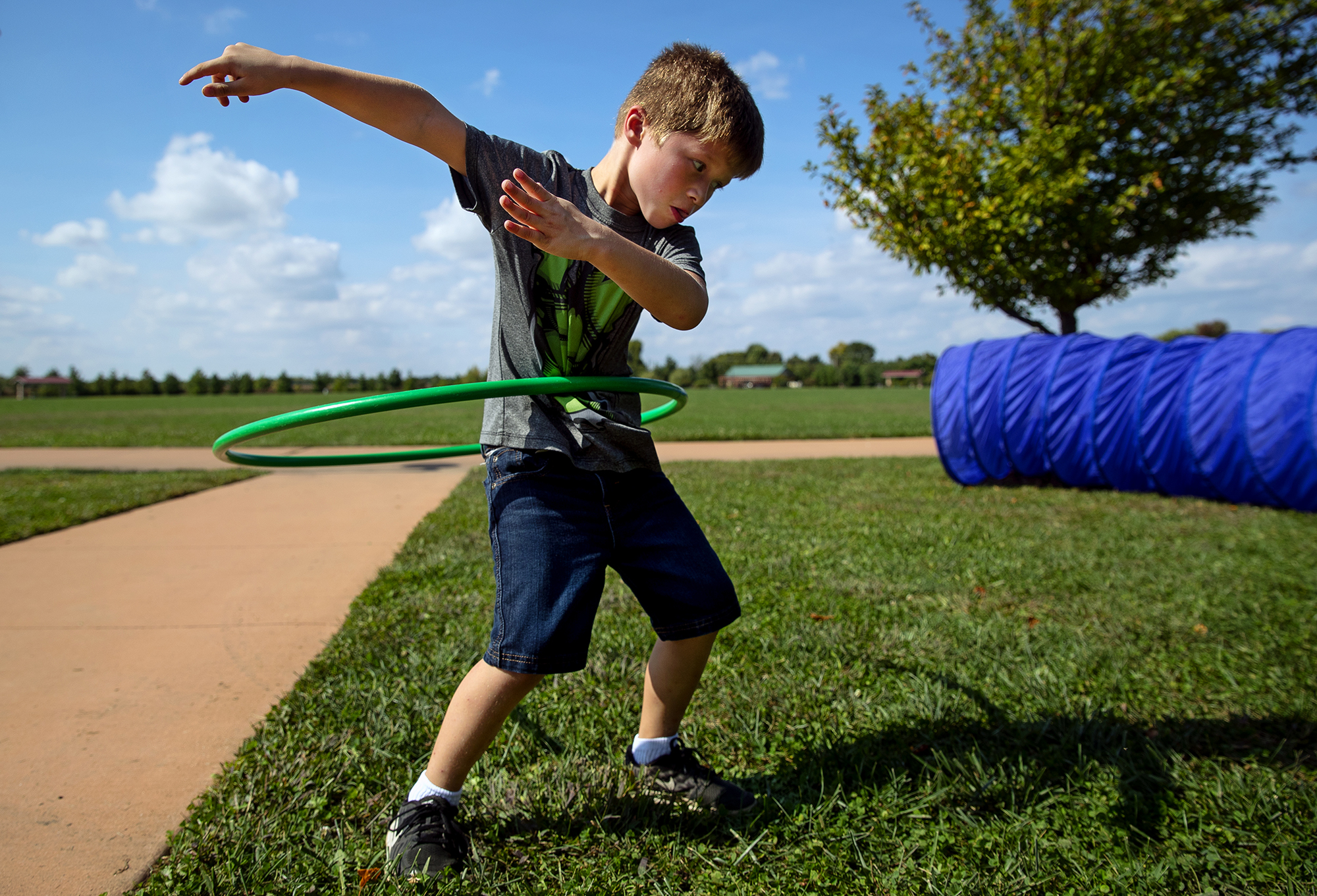 """Kamden Estes concentrates as he attempts to hula hoop during the """"Move 200"""" event at Southwind Park Sunday, Sept. 30, 2018. The genHkids station also featured a balance beam, a crawling tunnel and jump rope. The Illinois Bicentennial Coordinating Committee of Springfield has designated the month of October as Move 200 to interest the citizens of Springfield to exercise for 200 minutes in a month. [Ted Schurter/The State Journal-Register]"""