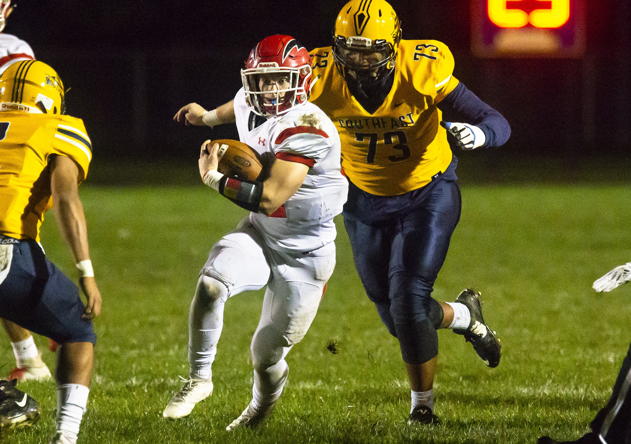 Glenwood's Austin Schiff breaks through the Southeast defense with the Spartan's Herb McMath in pursuit Friday, Oct. 12, 2018 at Southeast High School's Spartan Field in Springfield, Ill. [Rich Saal/The State Journal-Register]