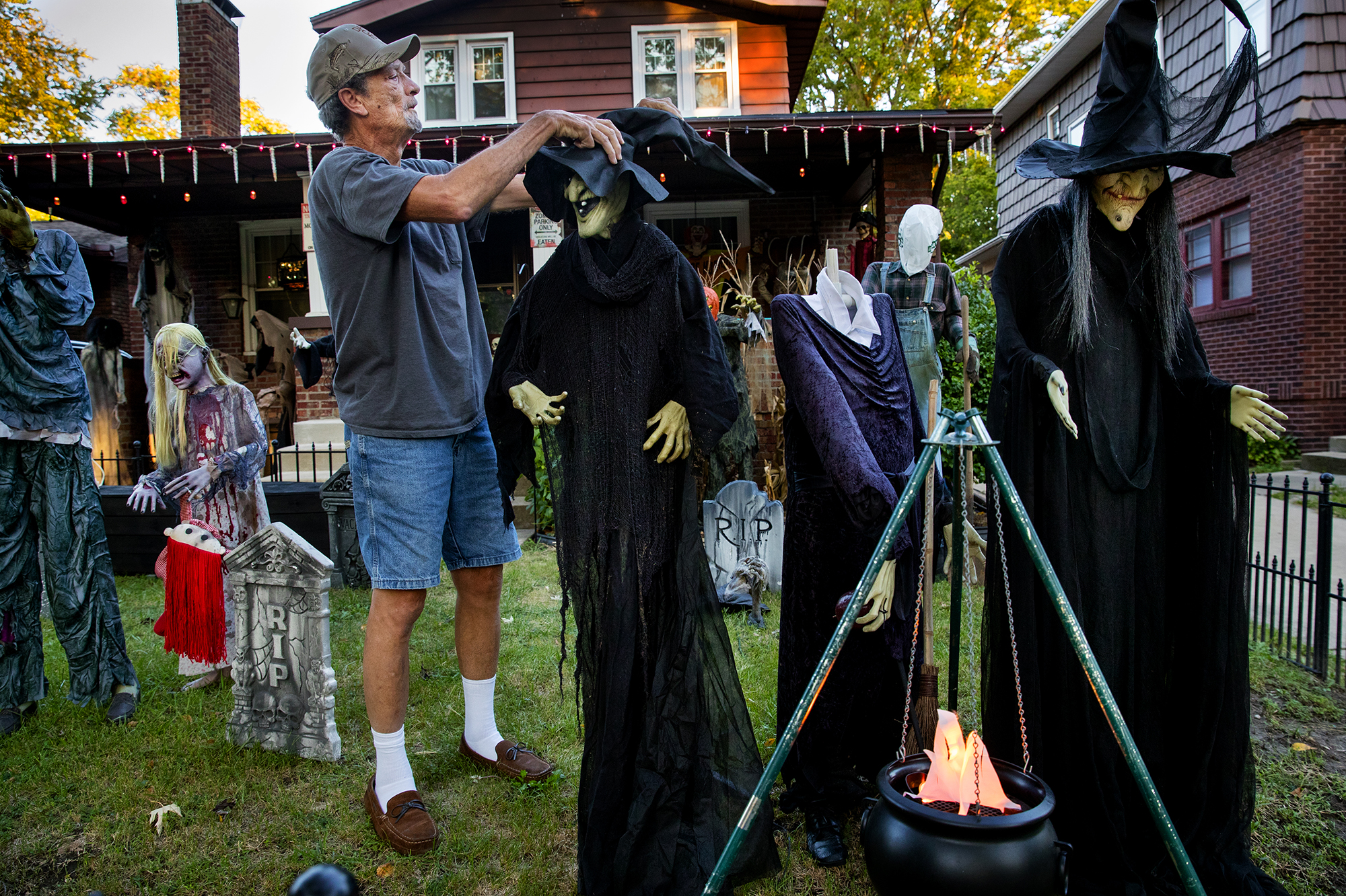 Mike West adjusts a witch's hat in his front yard Halloween display Monday, Oct. 8, 2018. West has been installing monsters in his yard for Halloween with the help of his children for about 25 years, a process he usually starts in mid to late September. The South Sixth Street display gets creepier at dusk as he illuminates the scene with extra lights. [Ted Schurter/The State Journal-Register]