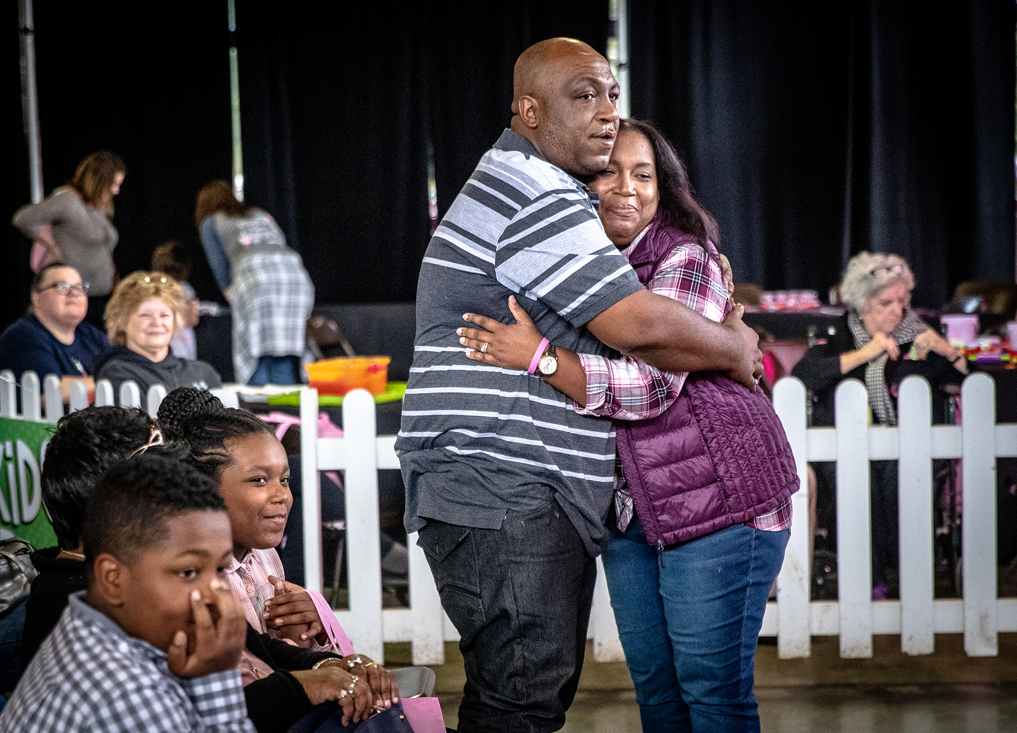 Tamiko Bilbro-Nicholson, right, gets a hug from her husband, Adarian Nicholson, left, after being recognized as one of the three Super Survivors during Memorial Medical Center's Be Aware Women's Fair in the Orr Building at the Illinois State Fairgrounds, Saturday, Oct. 13, 2018, in Springfield, Ill. The Super Survivors are women that have battled breast cancer and their stories of have inspired others. [Justin L. Fowler/The State Journal-Register]