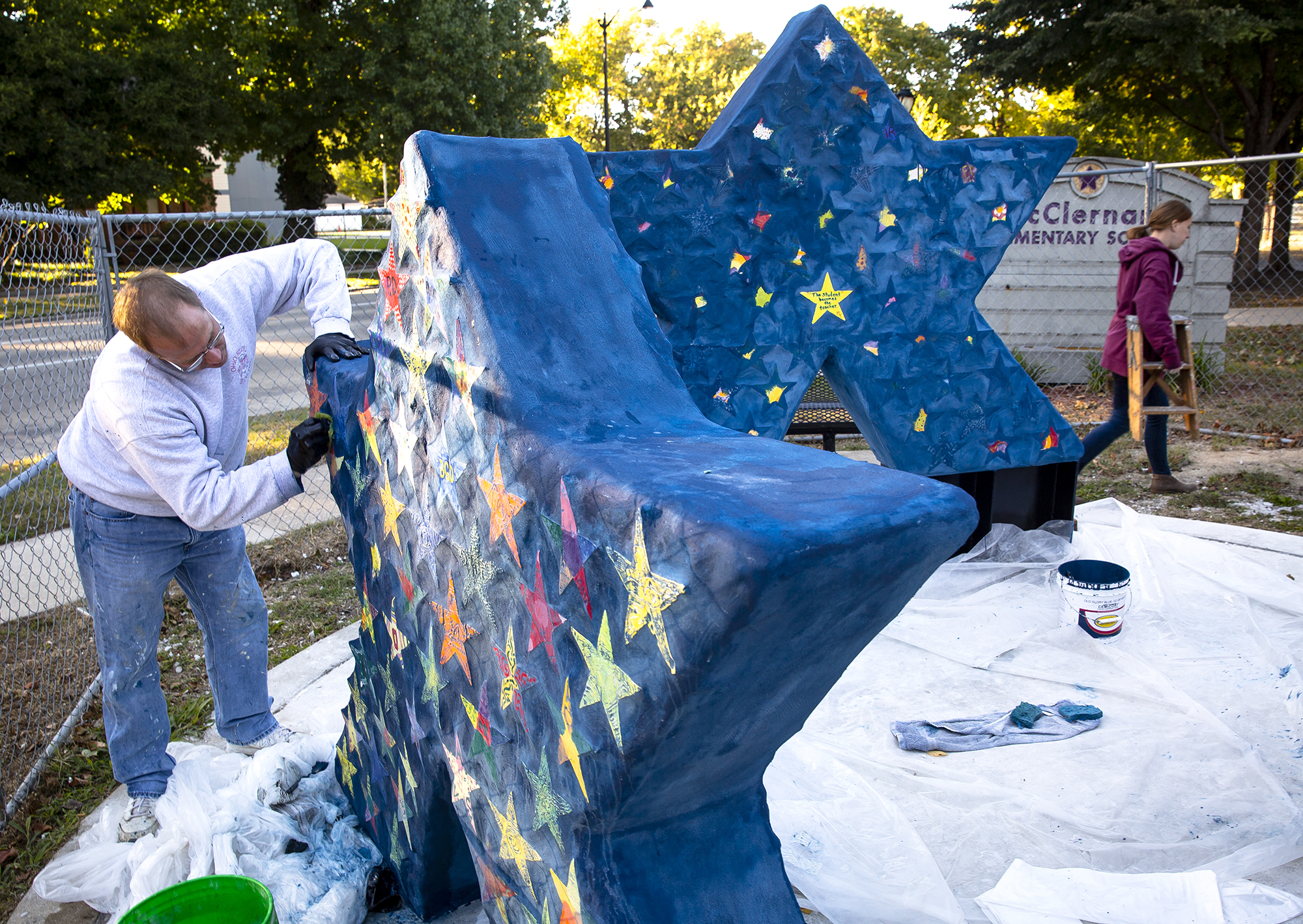 Tom George, a Springfield Art Association volunteer and board member, and Erin Svendsen, SAA education coordinator, worked on the finishing details of three large stars with inlaid glass tiles made by each of the students, faculty and staff at McClernand Elementary School Wednesday, Oct. 17, 2018 outside the school. It's the first art installation project that is part of the Bronwyn Eves Memorial School Art Project. Eves was a past SAA board president and volunteer who died in 2016. Her family and friends created the fund in her memory, which each year will build public art installations designed by students at schools throughout Sangamon County. The project is also part of the SAA's Art Outreach program. [Rich Saal/The State Journal-Register]