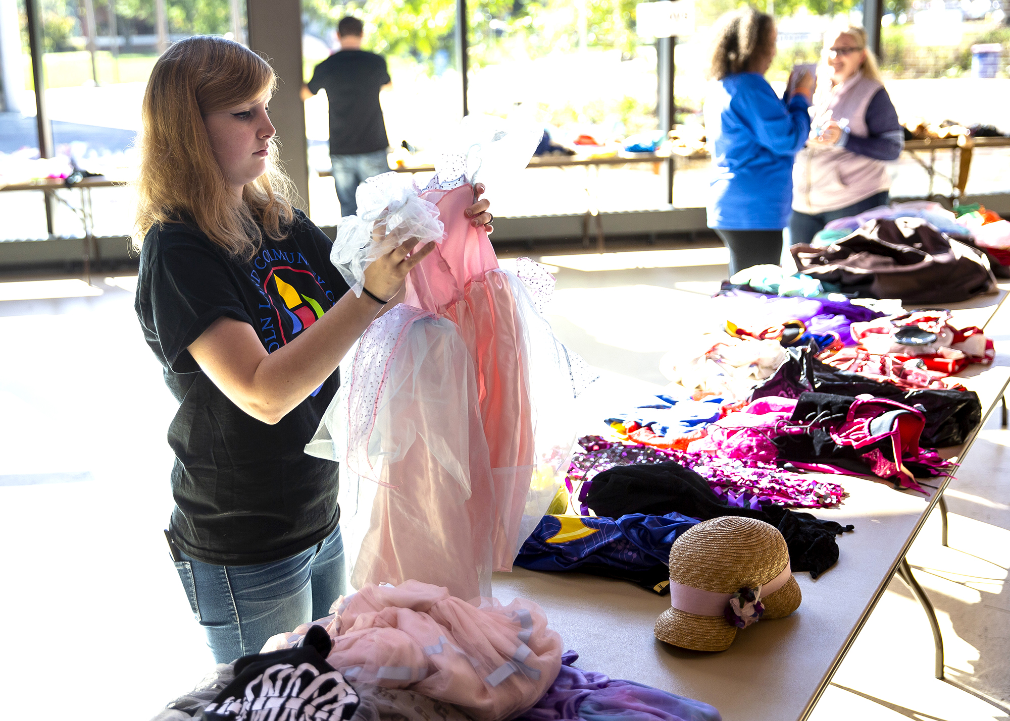 """Liz Davis sorts Halloween costumes on a table in the Lincolns Commons at Lincoln Land Community College during the Bootique costume giveaway Saturday, Oct. 20, 2018 in Springfield, Ill. Davis, an LLCC student who is the Honors Program president, came up with the idea last year to collect gently used costumes for families to pick up as needed. """"It's my favorite holiday and I wanted to share,"""" Davis says. The student organization this year collected 138 costumes and about 80 accessory pieces for the event. [Rich Saal/The State Journal-Register]"""