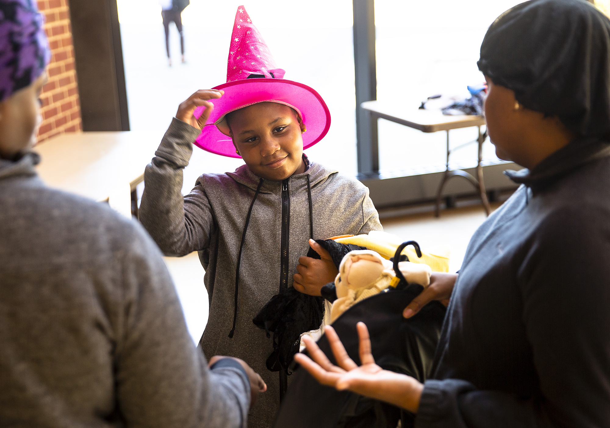 Akeria Scott, 9, tries on a witches hat for size during the Boutique Halloween costume giveaway Saturday, Oct. 20, 2018 in the Lincolns Commons at Lincoln Land Community College in Springfield, Ill. [Rich Saal/The State Journal-Register]