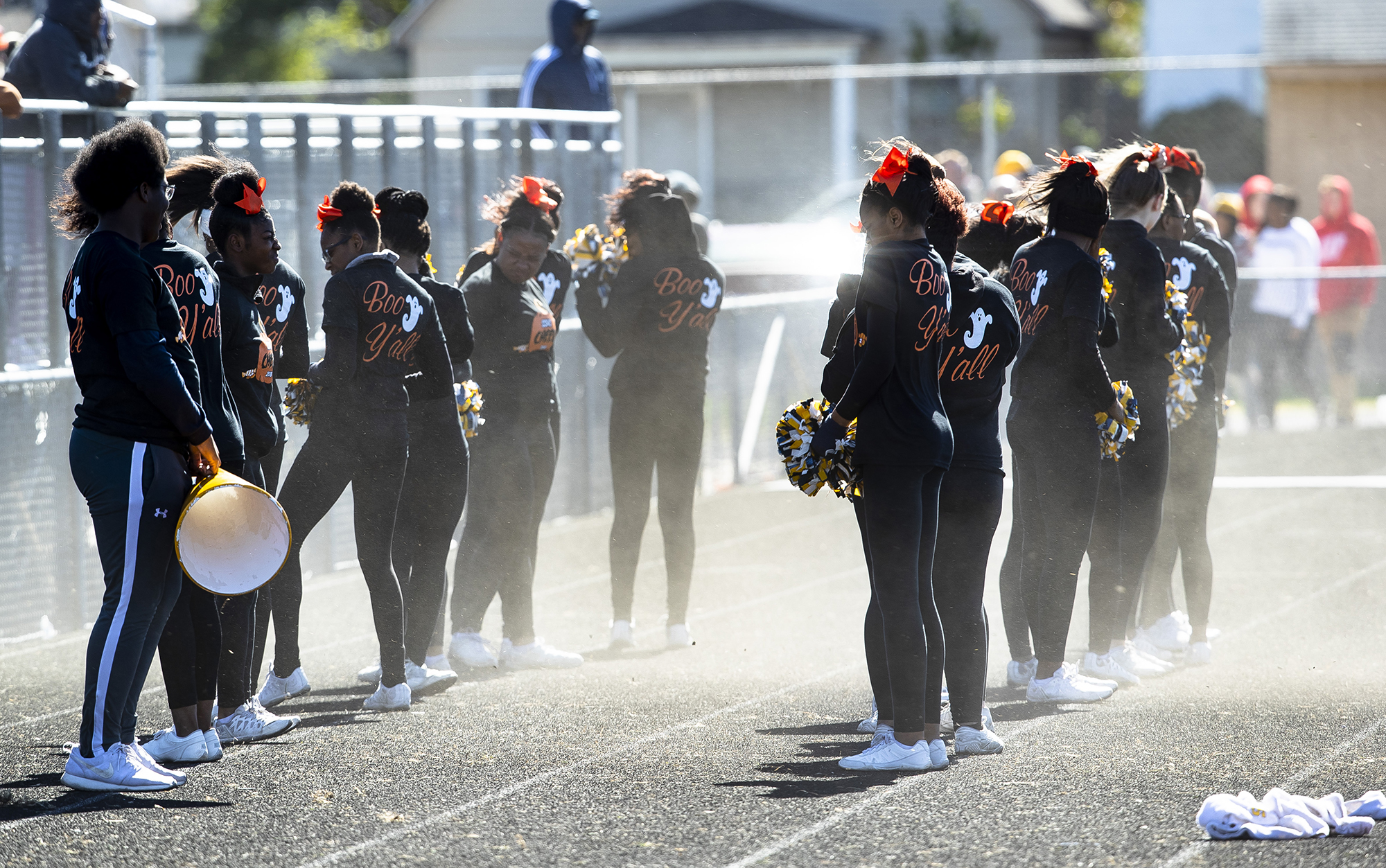 The Southeast High School cheer squad turns their back to the wind when it kicked up dust from the sidelines of the Southeast and Lanphier football game at Memorial Stadium Saturday, Oct. 20, 2018 in Springfield, Ill. [Rich Saal/The State Journal-Register]