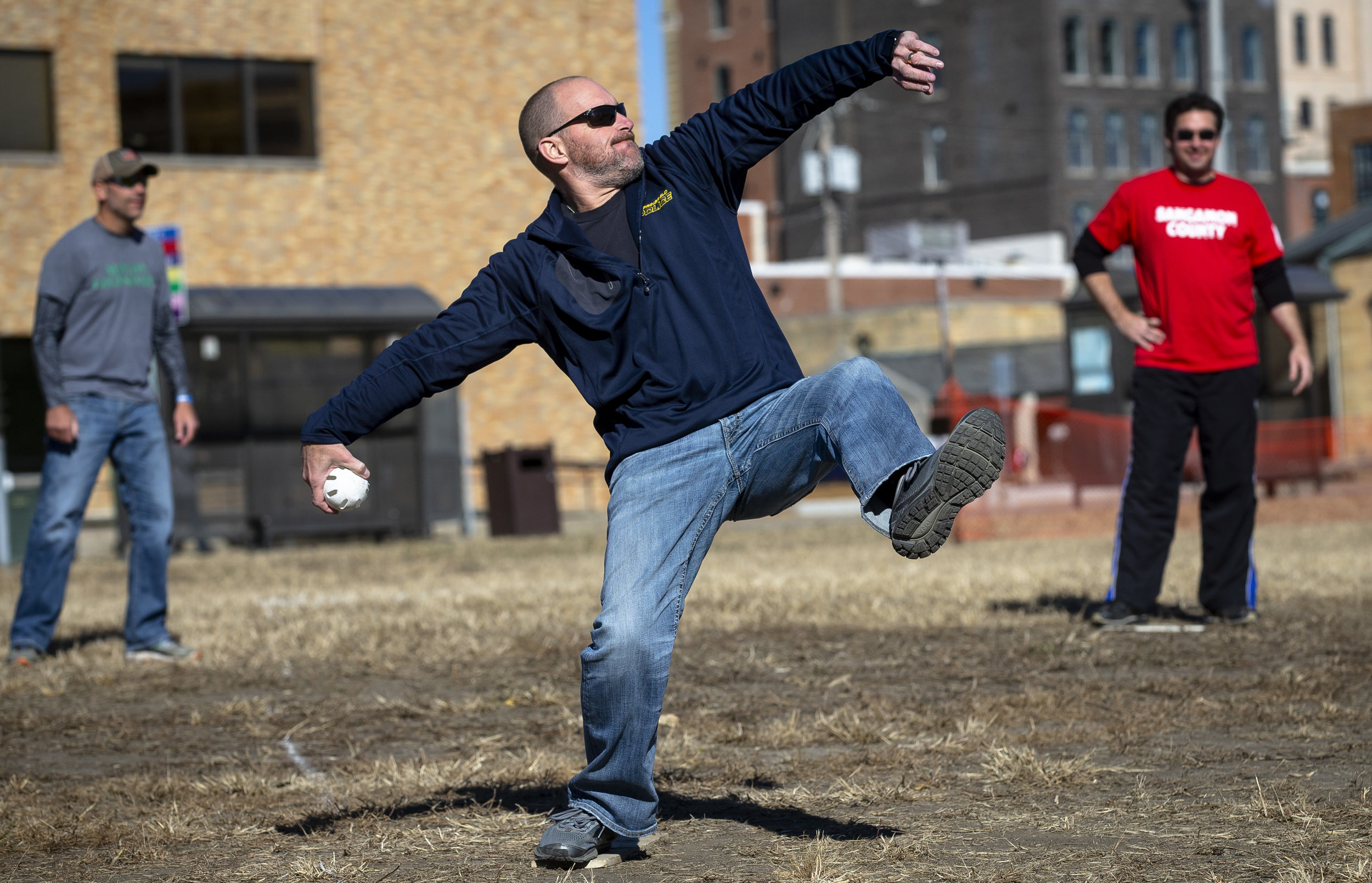 Springfield Police Assistant Chief Dyle Stokes winds up for the pitch in a whiffle ball game between city and county officials on the former YWCA block Sunday, Oct. 21, 2018  in Springfield, Ill. Money raised will benefit the Land of Lincoln Honor Flight.[Rich Saal/The State Journal-Register]