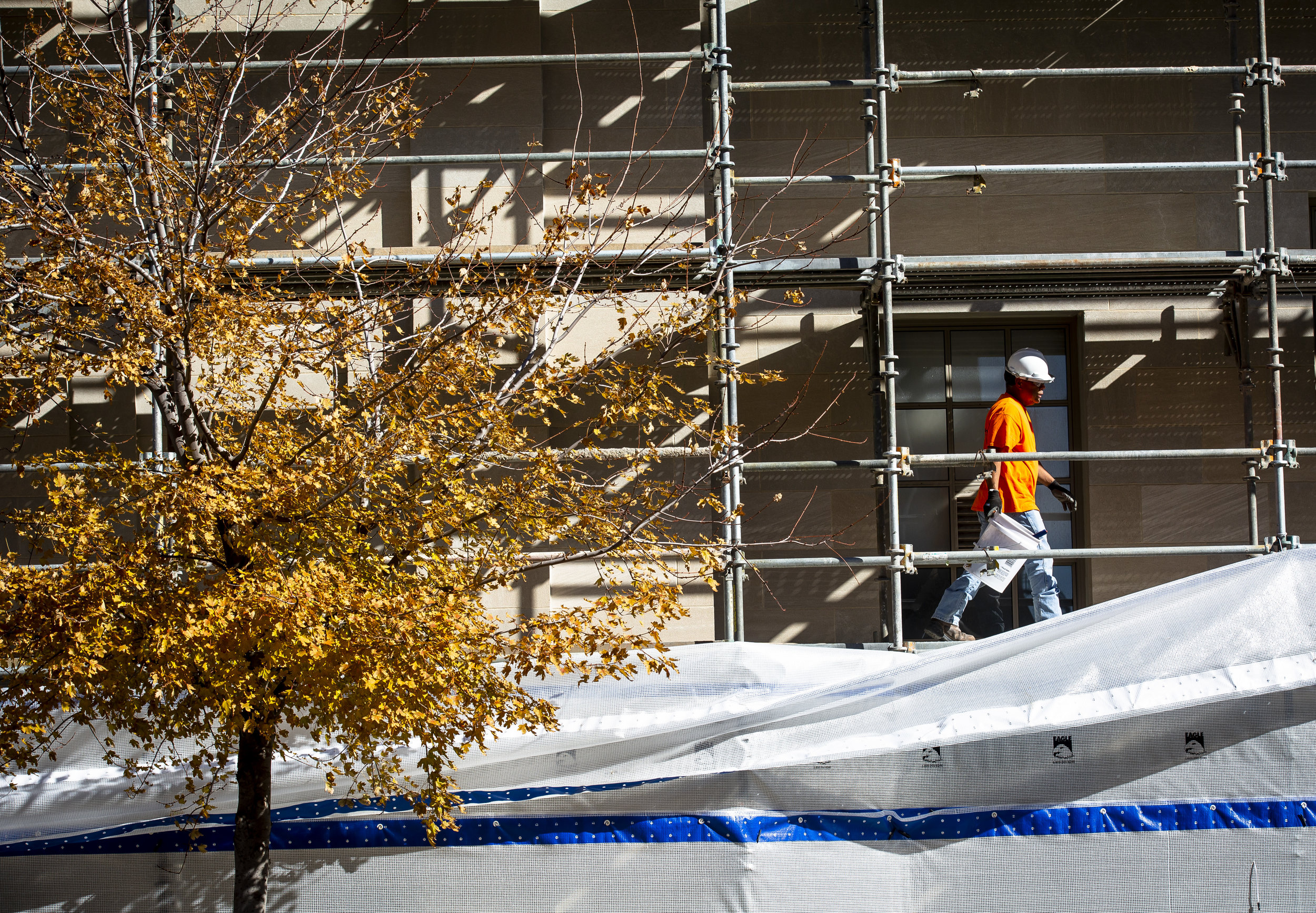 Erick Movataya works on removing the protective plastic wrap that has covered the west side of the Paul Findley Federal Building and U.S. Courthouse at 600 E. Monroe St. Tuesday, Oct. 23, 2018  in Springfield, Ill. The work on the west facade is part of a $2.6 million project to clean and repair the exterior limestone walls and terra cotta cornice, and will continue next year on the front and east sides. The building was built in 1930. [Rich Saal/The State Journal-Register]