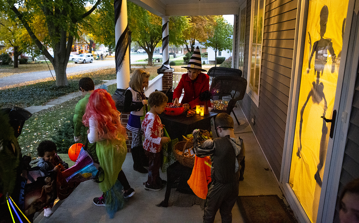 Anna May Fawns, 84, dishes up witches brew (purple Kool-Aid) and other goodies to trick or treaters from the porch of her daughter and son-in-law's home Wednesday, Oct. 31, 2018 in Williamsville, Ill. Most of the people in town are used to seeing Fawns on the porch. She used to live in the house until her daughter's family bought it, and she's shared her Halloween cheer for close to 50 years, she says. [Rich Saal/The State Journal-Register]