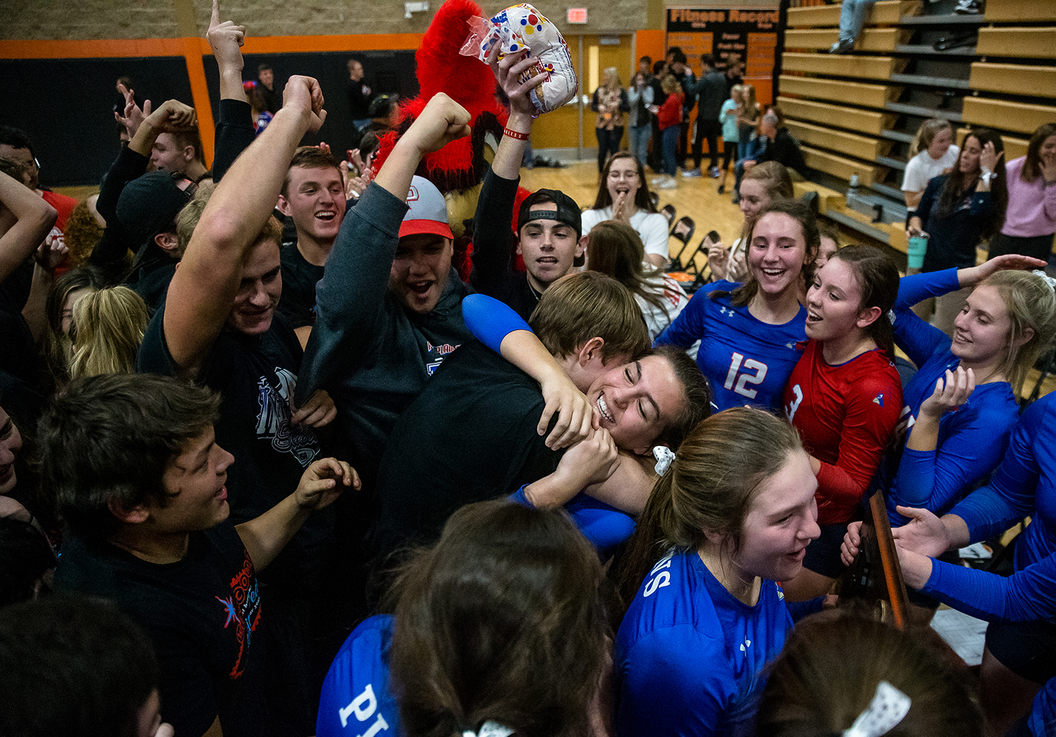 Pleasant Plains' Emma Grieser (5) is hugged by a member of the student section as they rush the floor to celebrate the Cardinals defeating Eureka in the Class 2A Beardstown Supersectional at Beardstown High School, Friday, Nov. 2, 2018, in Beardstown, Ill. [Justin L. Fowler/The State Journal-Register]