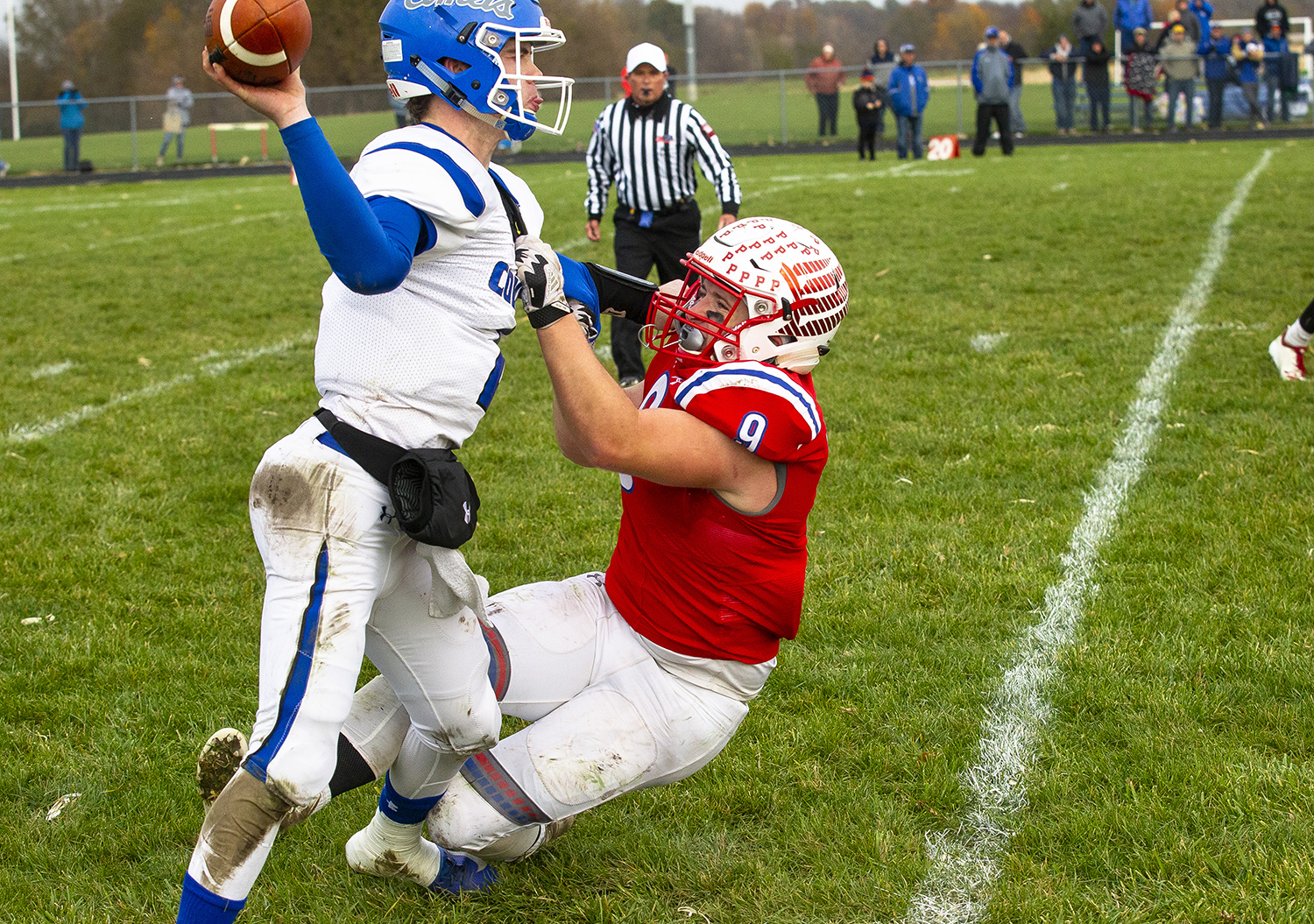Greenville quarterback Will Harnetiaux gets off a pass as Pleasant Plains' Jake Hermes try to pull him to the grounds during the Class 2A playoff game Saturday, Nov. 3, 2018 at Pleasant Plains High School in Pleasant Plains, Ill. [Rich Saal/The State Journal-Register]