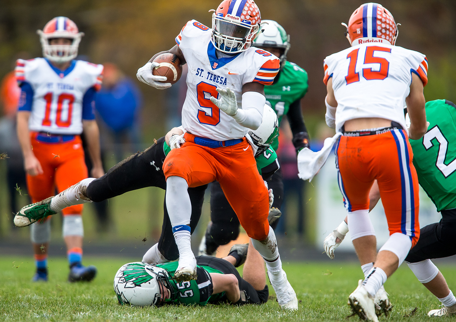 Decatur St. Teresa's Jacardia Wright (9) bursts through a tackle from Athens' Everett Shuck (55) on a rush in the first half in the second round of the Class 2A playoffs at Athens High School, Saturday, Nov. 3, 2018, in Athens, Ill. [Justin L. Fowler/The State Journal-Register]