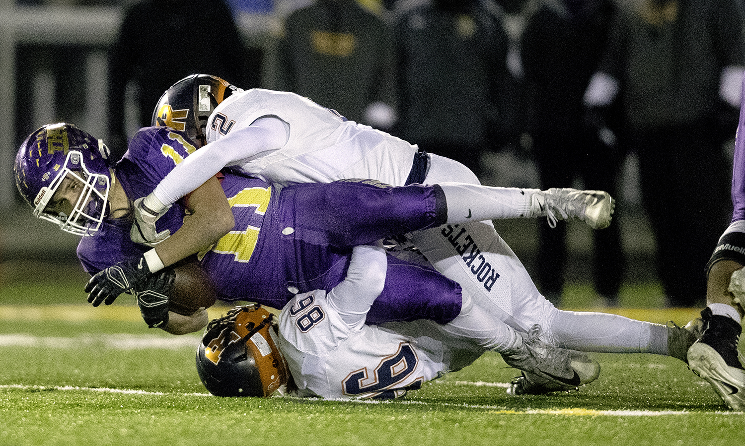 Taylorville's Brandon Odam is brought down by Rochester's Colton Rowden and Talon Williams during the Class 4A quarterfinals in Taylorville Saturday, Nov. 10, 2018. [Ted Schurter/The State Journal-Register]