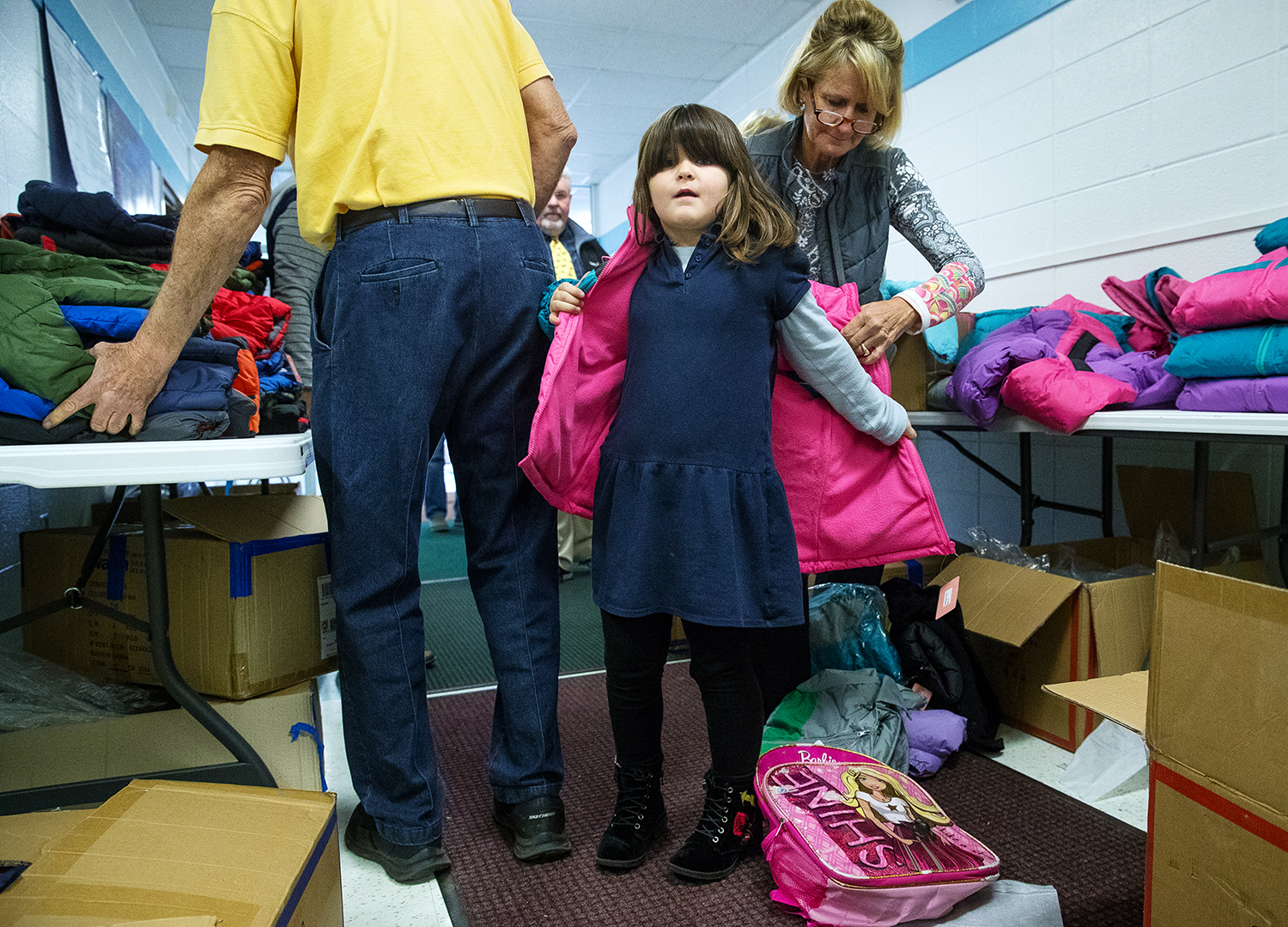 Chloe Harris is helped into a new coat by Liz Murer at Graham Elementary School Monday, Nov. 19, 2018. The Rotary Club of Springfield Sunrise brought more than 90 brand new coats for distribution at Graham Elementary School. Remaining coats will be distributed at Christmas holiday event and given to The Matthew Project. [Ted Schurter/The State Journal-Register]