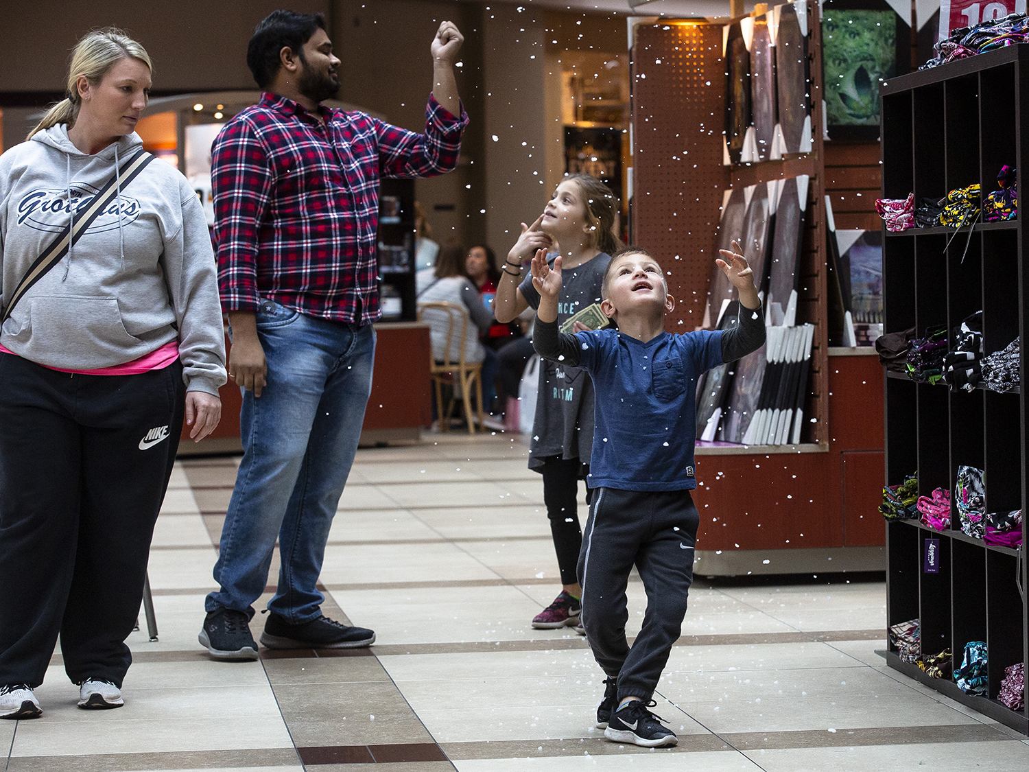 Brady Powers watches artificial snow fall from the ceiling in the center court of White Oaks Mall in Springfield, Ill. Friday, Nov. 23, 2018. Powers and his mother, Shauna, left, and his cousin Audrey Smith behind him, along with their extended family, were at the mall as part of their Black Friday shopping tradition. [Rich Saal/The State Journal-Register]