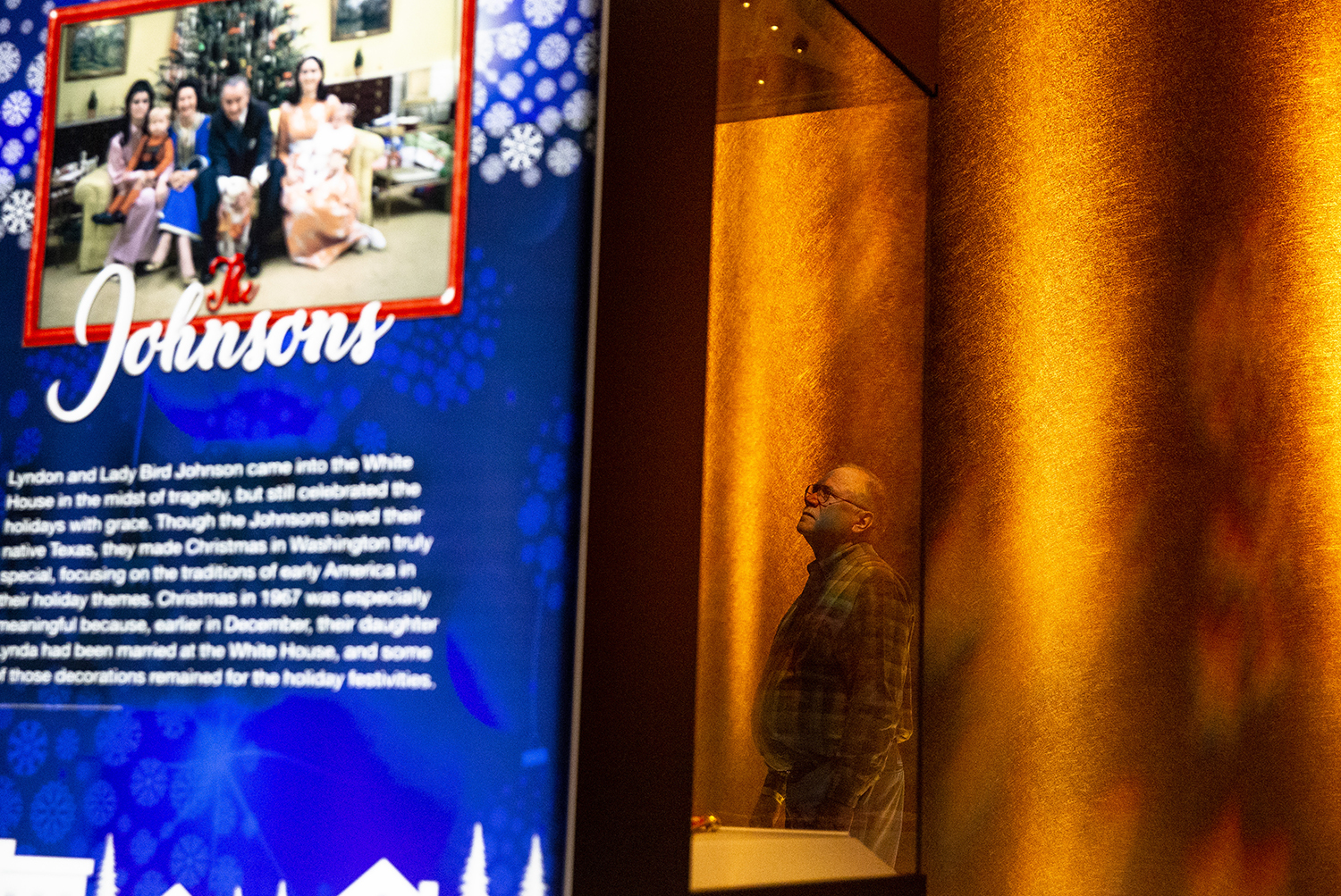 """Tom Schmidt watches a video on how different presidential administrations have celebrated Christmas, part of """"Holidays at the White House: A Presidential Christmas"""" Friday, Nov. 23, 2018 in the Treasures Gallery at the Abraham Lincoln Presidential Library in Springfield, Ill. It features decorations, photographs and gifts from the administrations of Lyndon Johnson, Richard Nixon, Gerald Ford and George H. W. Bush and runs through Jan. 6, 2019. [Rich Saal/The State Journal-Register]"""