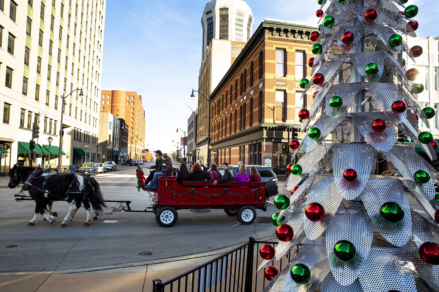 A horse drawn carriage passes the community Christmas tree on its way around the downtown square on the first of this year's Old Capitol Holiday Walks sponsored by DSI Springfield Saturday, Nov. 24, 2018 in Springfield, Ill. It was also Small Business Saturday, with nearly a dozen new shops open since last year. The Holiday Walks will continue every Saturday from noon to 5 p.m. and every Wednesday from 5-8 p.m. through Dec. 22. The carriage rides were provided by Red Gate Farm and the Christmas tree was built and donated by Ace Sign Co. [Rich Saal/The State Journal-Register]