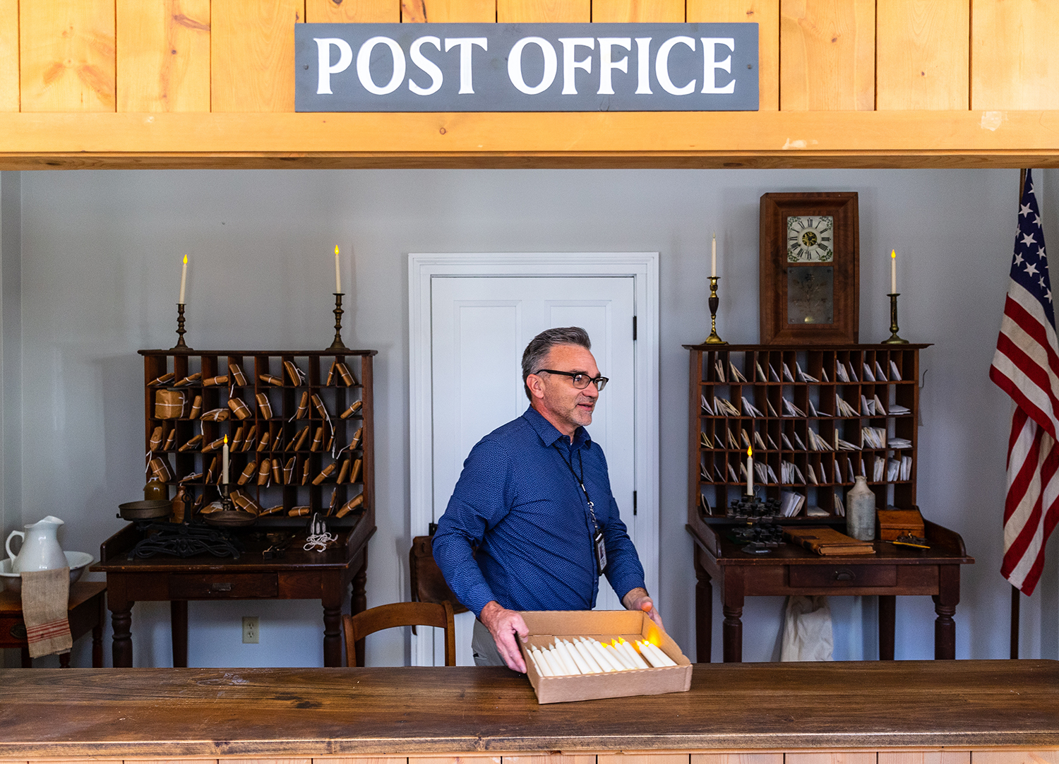 Troy Gilmore, the Site Superintendent for the State Historic Sites of Springfield, places battery operated candles throughout a replica of a post office on the first floor of the three story building that once housed the Lincoln-Herndon Law Offices that has now become the tourist welcome center for the Springfield Convention and Visitors Bureau, Wednesday, Nov. 21, 2018, in Springfield, Ill. [Justin L. Fowler/The State Journal-Register]