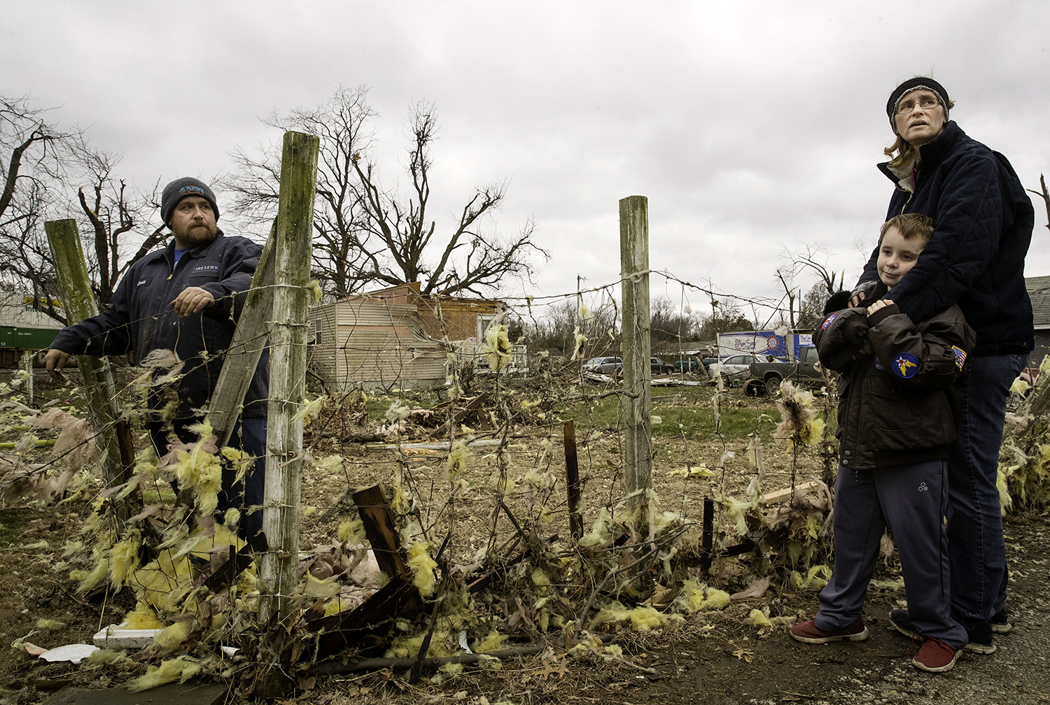 David Bowers, left, his son David and wife Tammy gather at the edge of their property in Taylorville after assessing the tornado damage to their home Sunday, Dec. 2, 2018. The family took shelter in the basement while the storm tore the roof completely off their house. [Ted Schurter/The State Journal-Register]