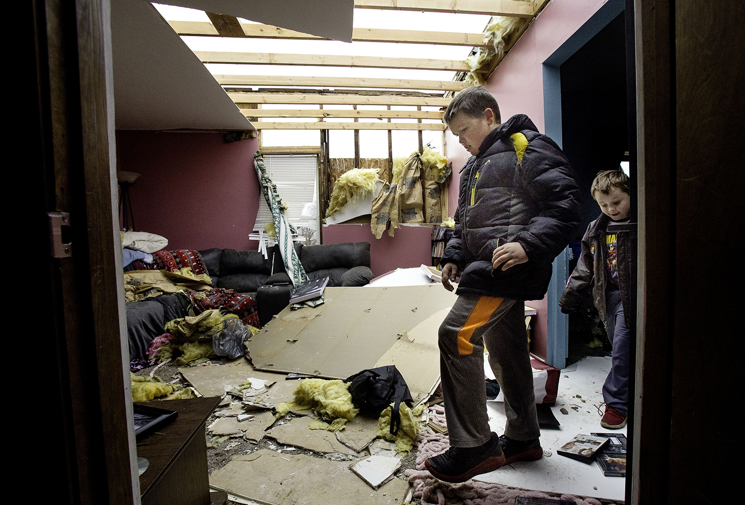 Tim Mayes and his cousin David Bowers step gingerly through the interior of Bowers' tornado damaged Taylorville home Sunday, Dec. 2, 2018. The roof of their home was completely torn off by the storm. [Ted Schurter/The State Journal-Register]