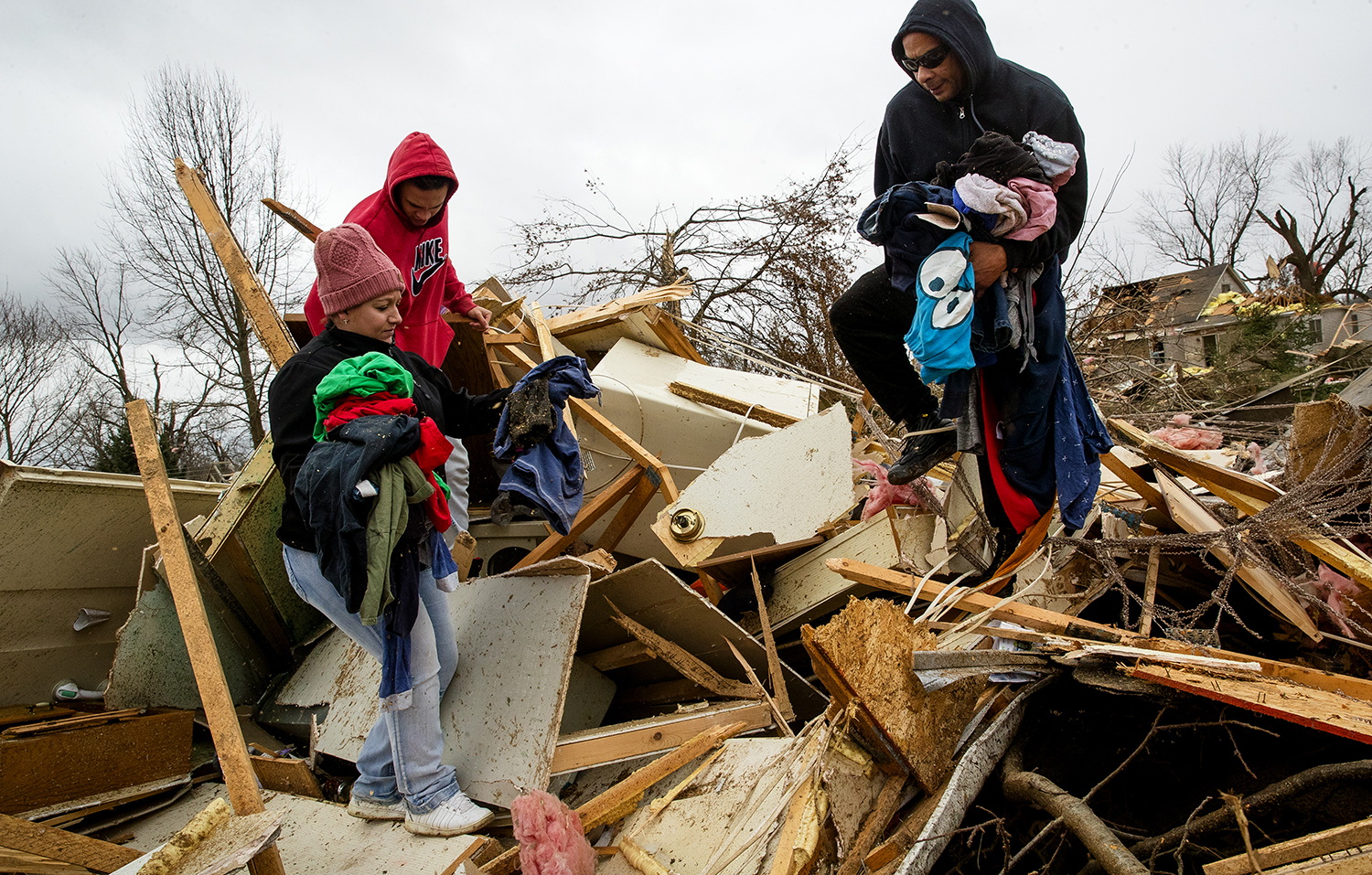 Katie Schafer, left, Marquice Barbour and George Bailey Sr. help sort through the debris for salvageable items from Tiffani Bailey's tornado-damaged house in in Taylorville Sunday, Dec. 2, 2018. [Ted Schurter/The State Journal-Register]
