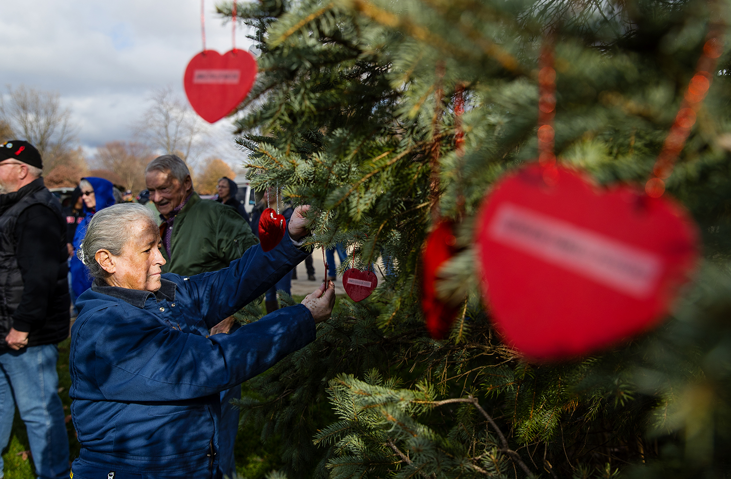 Susie Justus places an ornament on a tree during A Christmas Remembrance ceremony at the Vietnam Veterans Memorial at Oak Ridge Cemetery Saturday, Dec. 1, 2018. The Air Force veteran was joined by others who placed heart-shaped ornaments as the names of troops listed as prisoner of war or missing in action was read aloud. The Land of Lincoln Chorus provided music for the annual service. [Ted Schurter/The State Journal-Register]