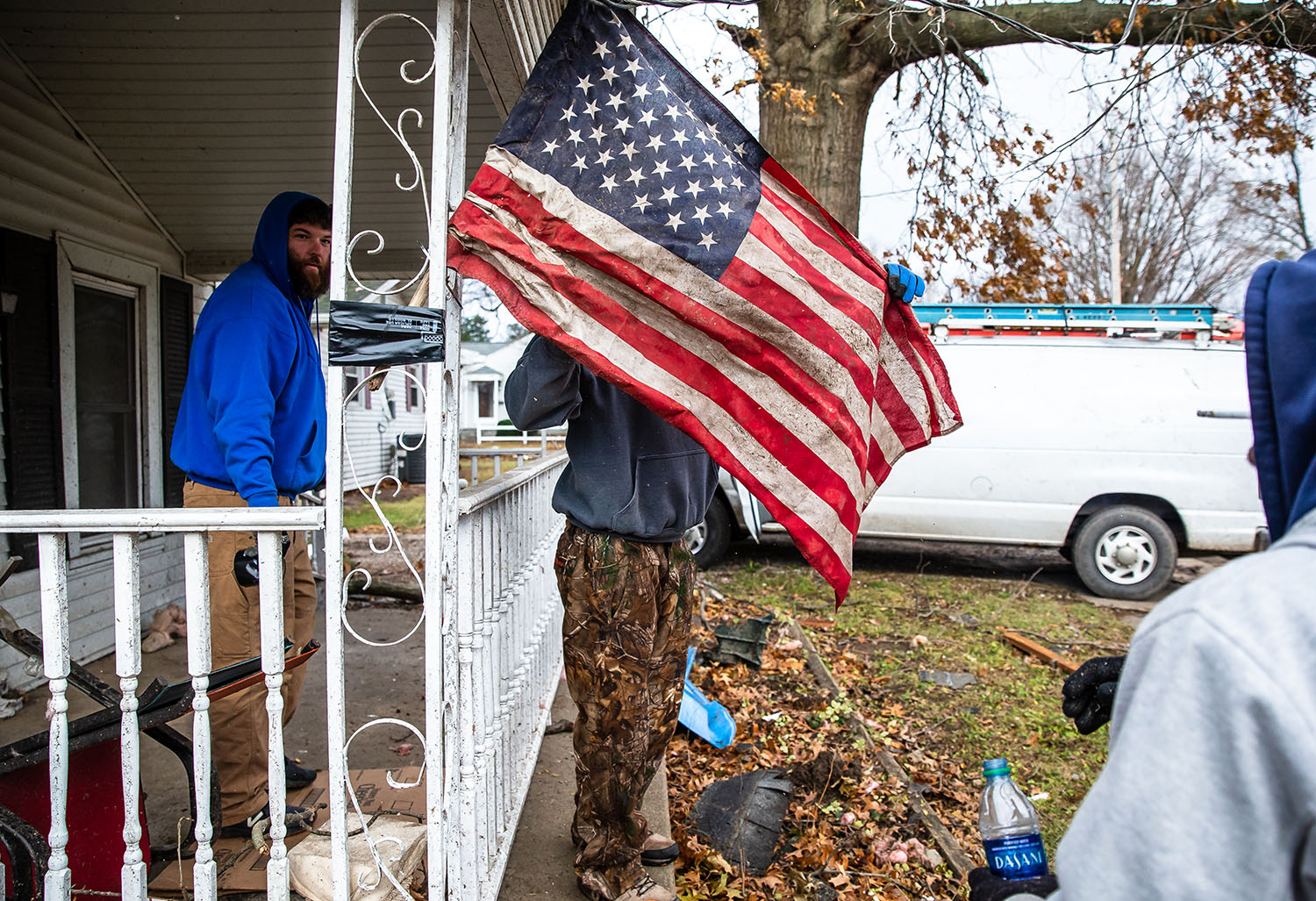 "Kris Newby, owner of Newby Construction Solutions, center unfurls an American Flag that he found in the mud and rehung with the help of Keith Westbrook, left, and Jimmy Koonce, right, on the front porch of a home that had lost a portion of it's roof from Saturday's tornado as cleanup continues along West Prairie Street, Monday, Dec. 3, 2018, in Taylorvile, Ill. ""It's the American Flag, you can't let it lay there in the mud,"" said Newby who found the flag after putting a tarp on the home's roof. [Justin L. Fowler/The State Journal-Register]"