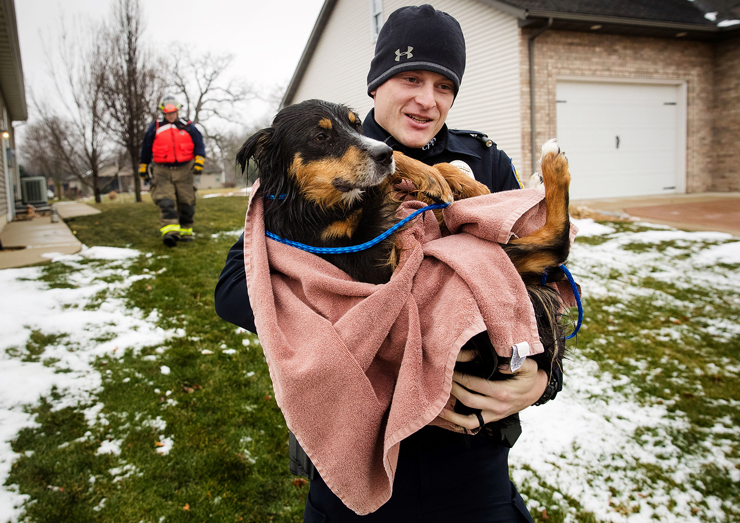 Chatham Police Officer Jacob Bouldin carries a dog that was rescued from an icy pond behind Turtle Cove in Chatham by Lauren Staab Monday, Jan. 8, 2018. Staab used a plastic boat to make her way to the dog and scoop him up before getting him inside to warm up. [Ted Schurter/The State Journal-Register]