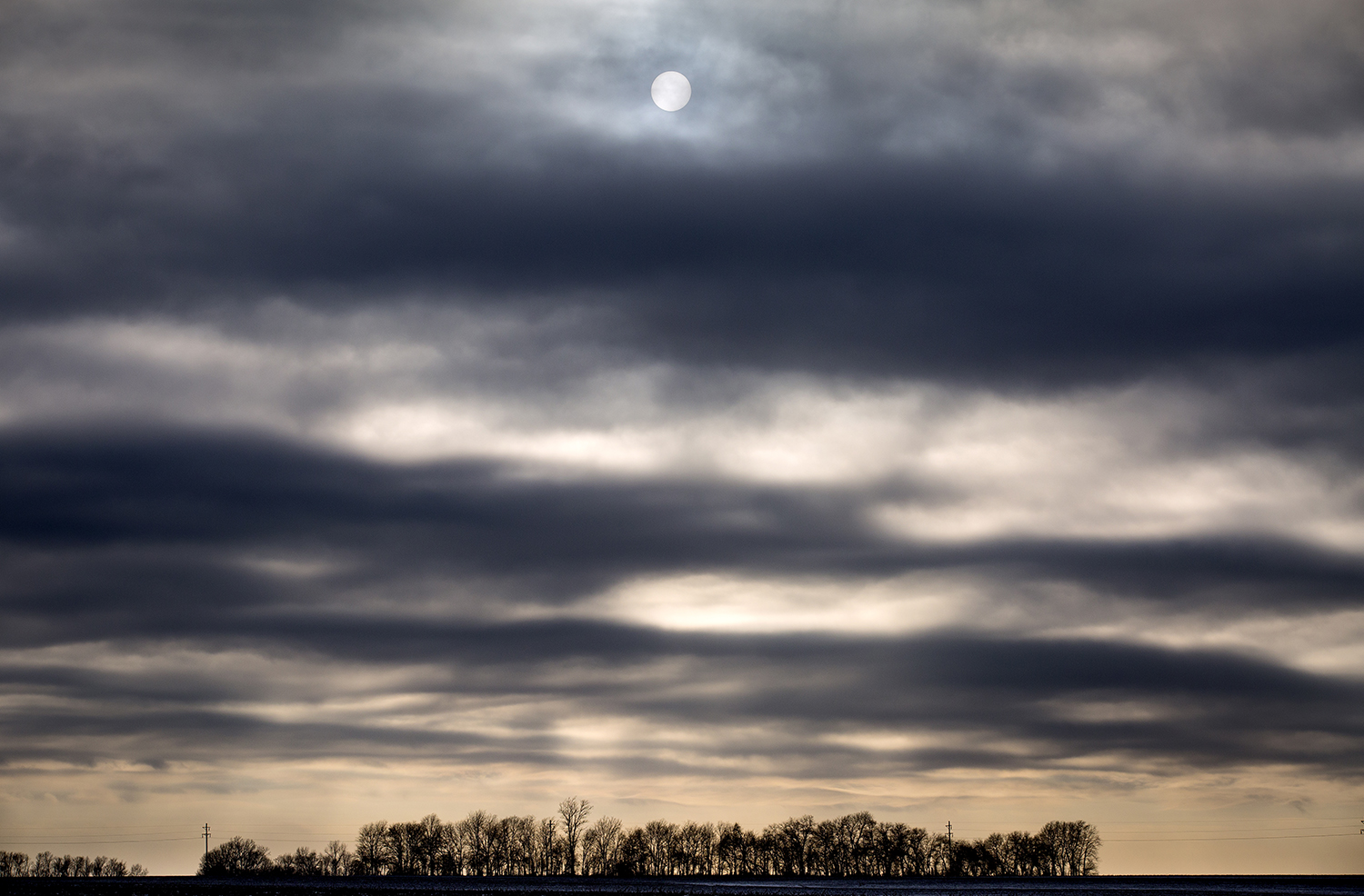 The sun peeks through layered clouds Tuesday, Jan. 16, 2018 near Berlin Tower Road in western Sangamon County. [Rich Saal/The State Journal-Register]