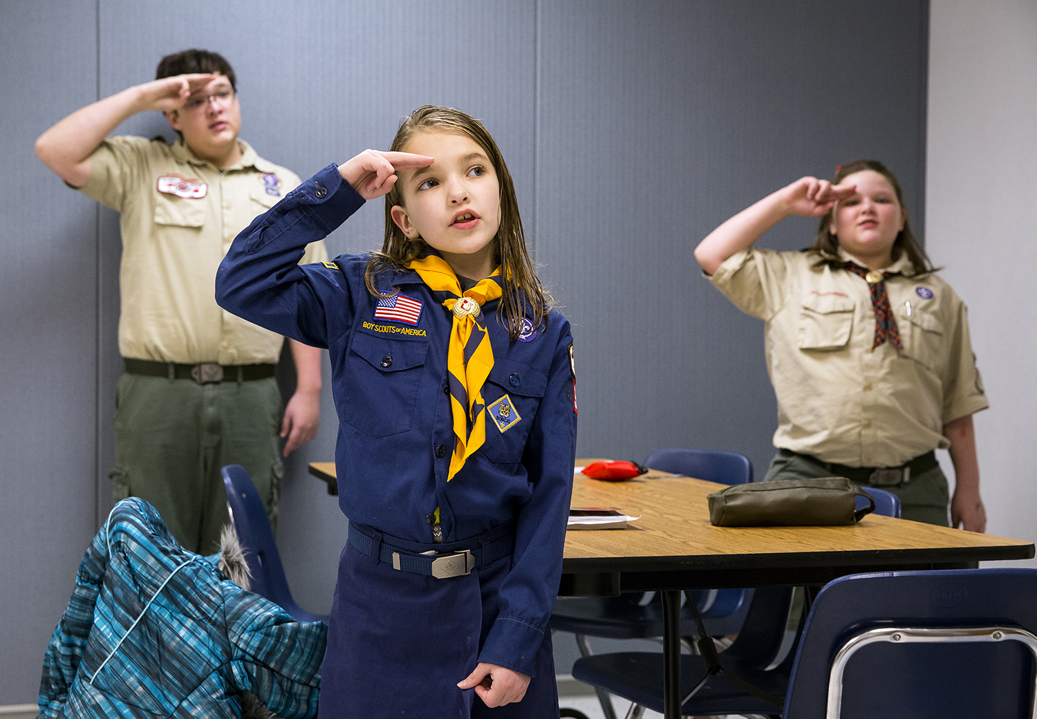 Natasha O'Brien salutes the flag during the Pledge of Allegiance at the start of Cub Scout Pack 38's meeting Thursday, Feb. 16, 2018 at St. John's Lutheran Church. O'Brien and Alison Higginson, right, are members of Springfield's first Cub Scout den to welcome girls as members. Alison's brother, Clay, left, a member of Boy Scout Troop 210, helped teach a first aid lesson during the meeting. [Rich Saal/The State Journal-Register]