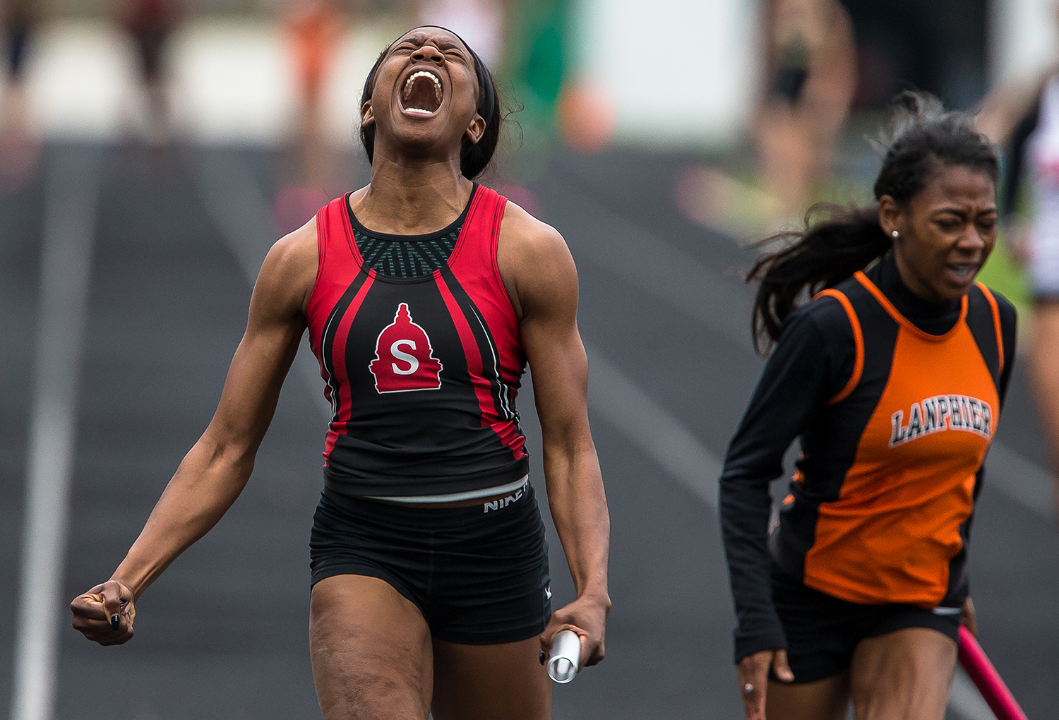 Springfield High's Ozzy Erewele screams after crossing the finish line first in the 4x100-meter relay during the Girls Central State Eight Track and Field Meet at Eisenhower High School on May 3. [Justin L. Fowler/The State Journal-Register]