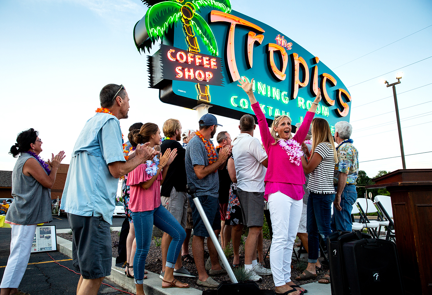 Tami Goodrich cheers when the sign from her parent's former restaurant, The Tropics in Lincoln, lights up for the first time in 15 years during a ceremonial relighting  Sunday, June 24, 2018. Lew and Bev Johnson ran the restaurant on Route 66 from 1953 to 1997 when they sold it. It closed for good in 2003. Ace Sign Co. in Springfield did the $70,000 restoration, which included replacing the original electrical system and some rusted panels and repainting the sign. Goodrich was joined by her siblings and nieces and nephews to turn the switch. [Rich Saal/The State Journal-Register]