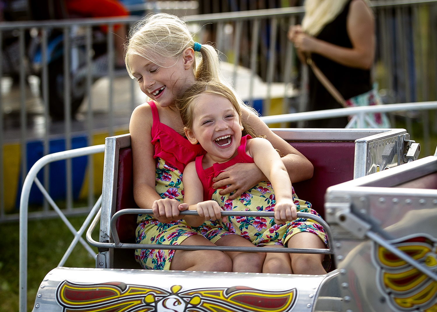 Hazle Smith, 8, holds on tight to her sister, Eve Haggard, 3, as they are spun around in an amusement ride in the carnival during Menard County Fair, Wednesday, July 18, 2018, in Petersburg, Ill. The fair continues on Thursday with the Barnyard Olympics and Animal Scrambles and goes through Sunday, July 22nd. [Justin L. Fowler/The State Journal-Register]