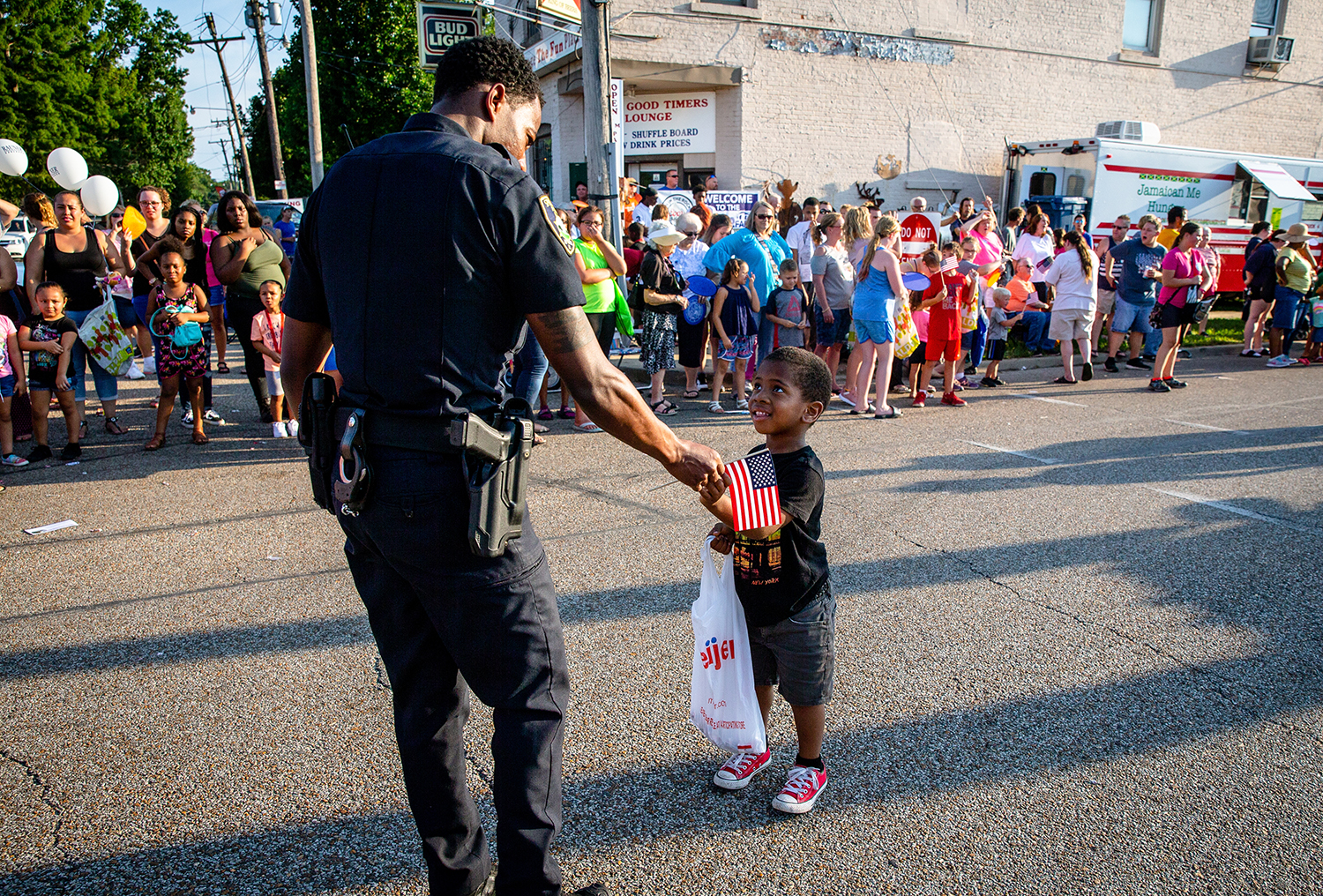 Springfield Police Officer Lamar Moore hands an American Flag to a young boy as he helps him out of the street as the parade enters the Main Gate during the Illinois State Fair Twilight Parade, Thursday, Aug. 9, 2018, in Springfield, Ill. [Justin L. Fowler/The State Journal-Register]