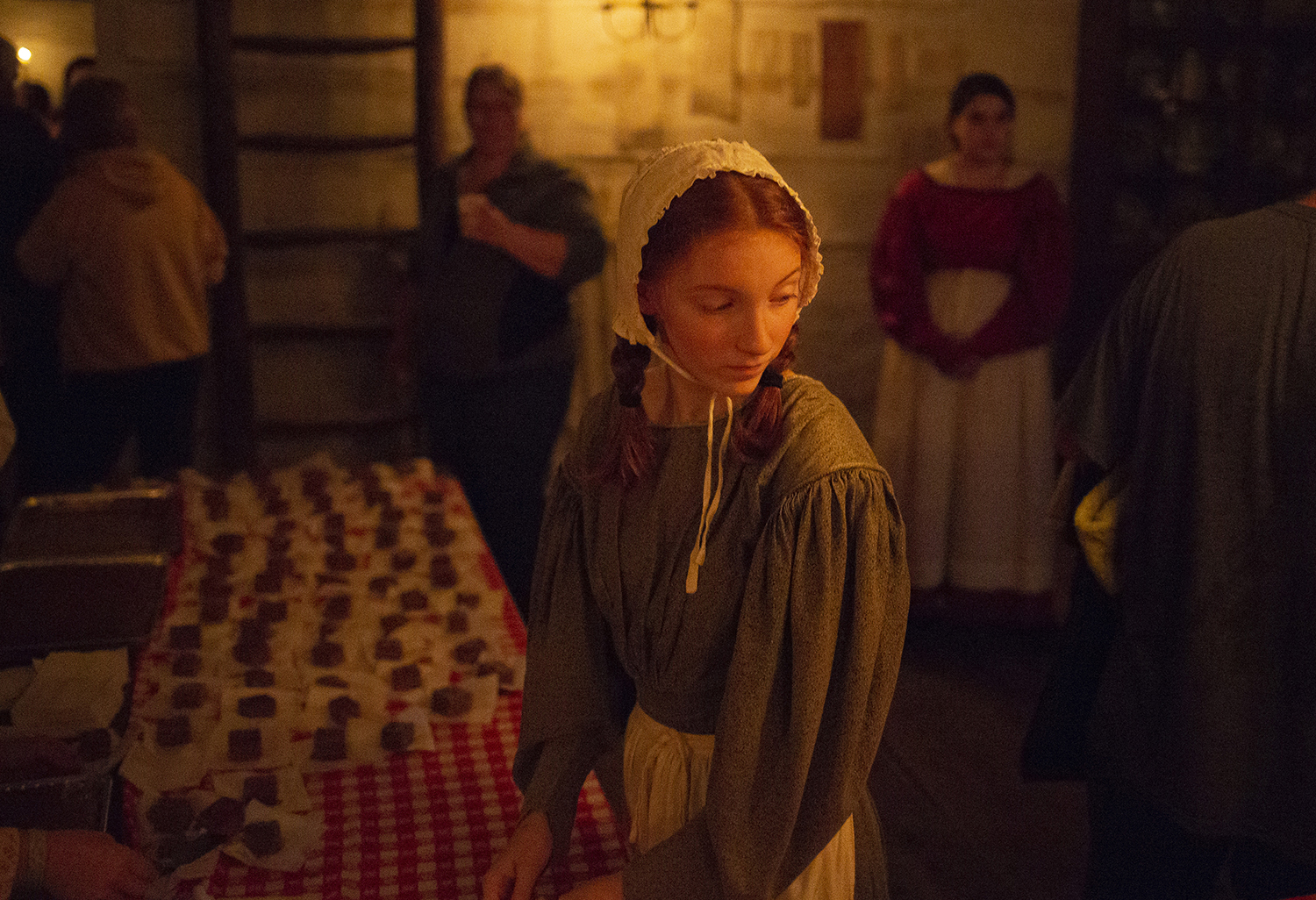 Gwen Chapman serves gingerbread in the Rutledge Tavern during the annual candlelight walk through Lincoln's New Salem State Historic Site Friday, Oct. 5, 2018, in Petersburg, Ill. [Rich Saal/The State Journal-Register]