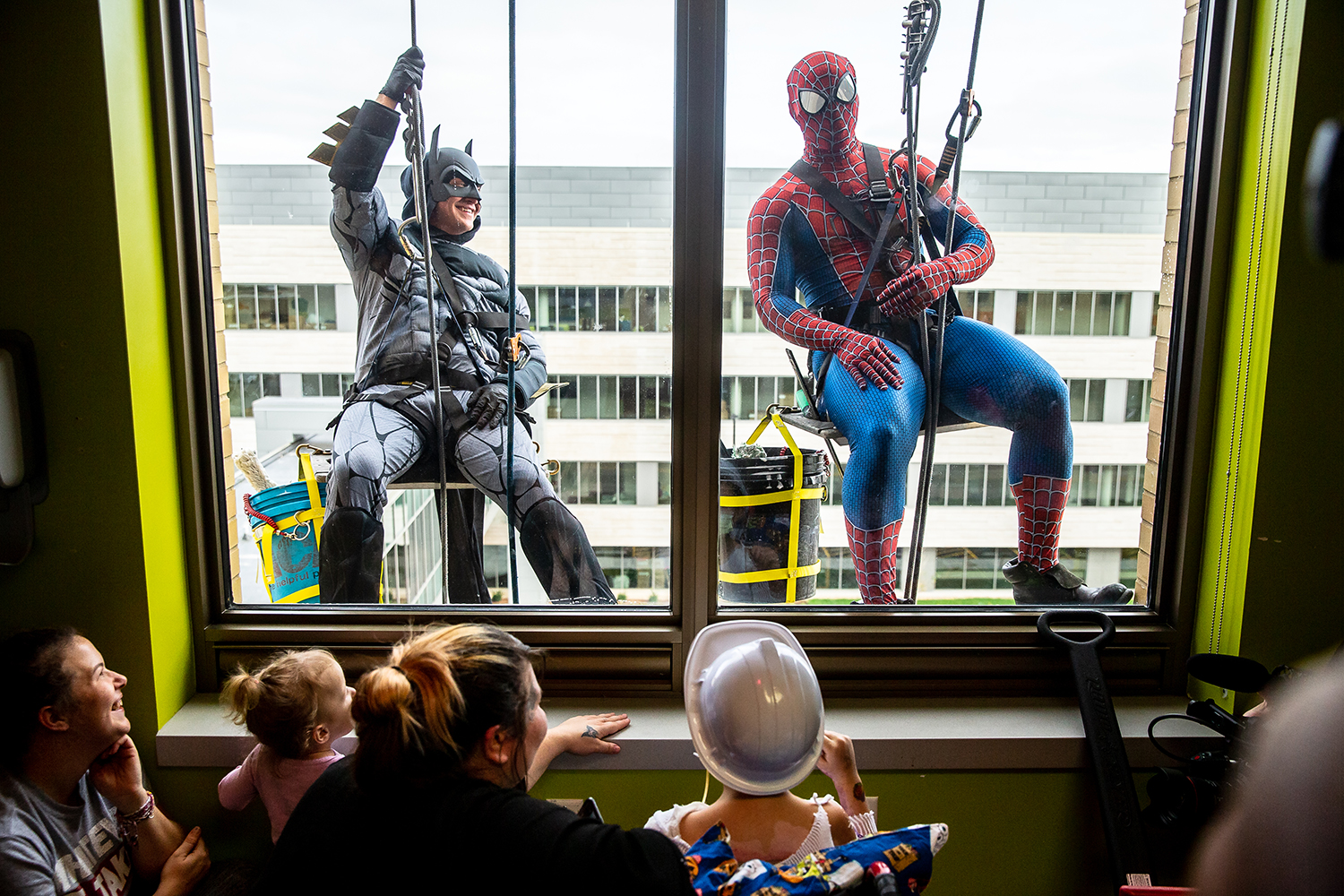 Batman, portrayed by Paul Soenksen, and Spiderman, portrayed by Roddrick Napier, bring a smile to children at HSHS St. John's Children Hospital as the superhero duo visit from outside as window washers courtesy of Maintenance Supply and O'Shea Builders, Thursday, Nov. 8, 2018, in Springfield, Ill. [Justin L. Fowler/The State Journal-Register]