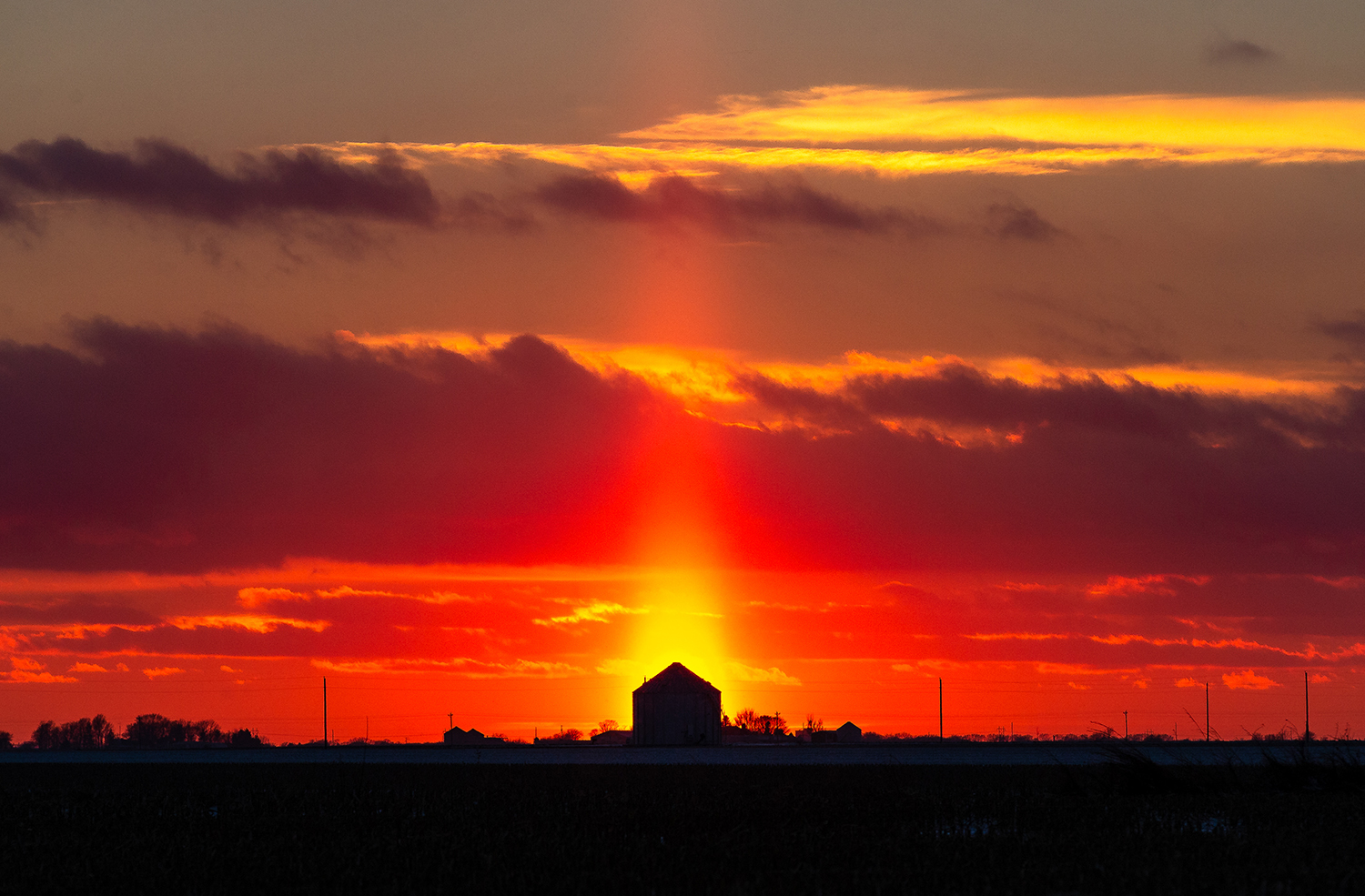 The setting sun casts a ray of light through the sky as it heads below the horizon behind a grain bin near Farley Road, Tuesday, Nov. 27, 2018, north of Loami, Ill. [Justin L. Fowler/The State Journal-Register]