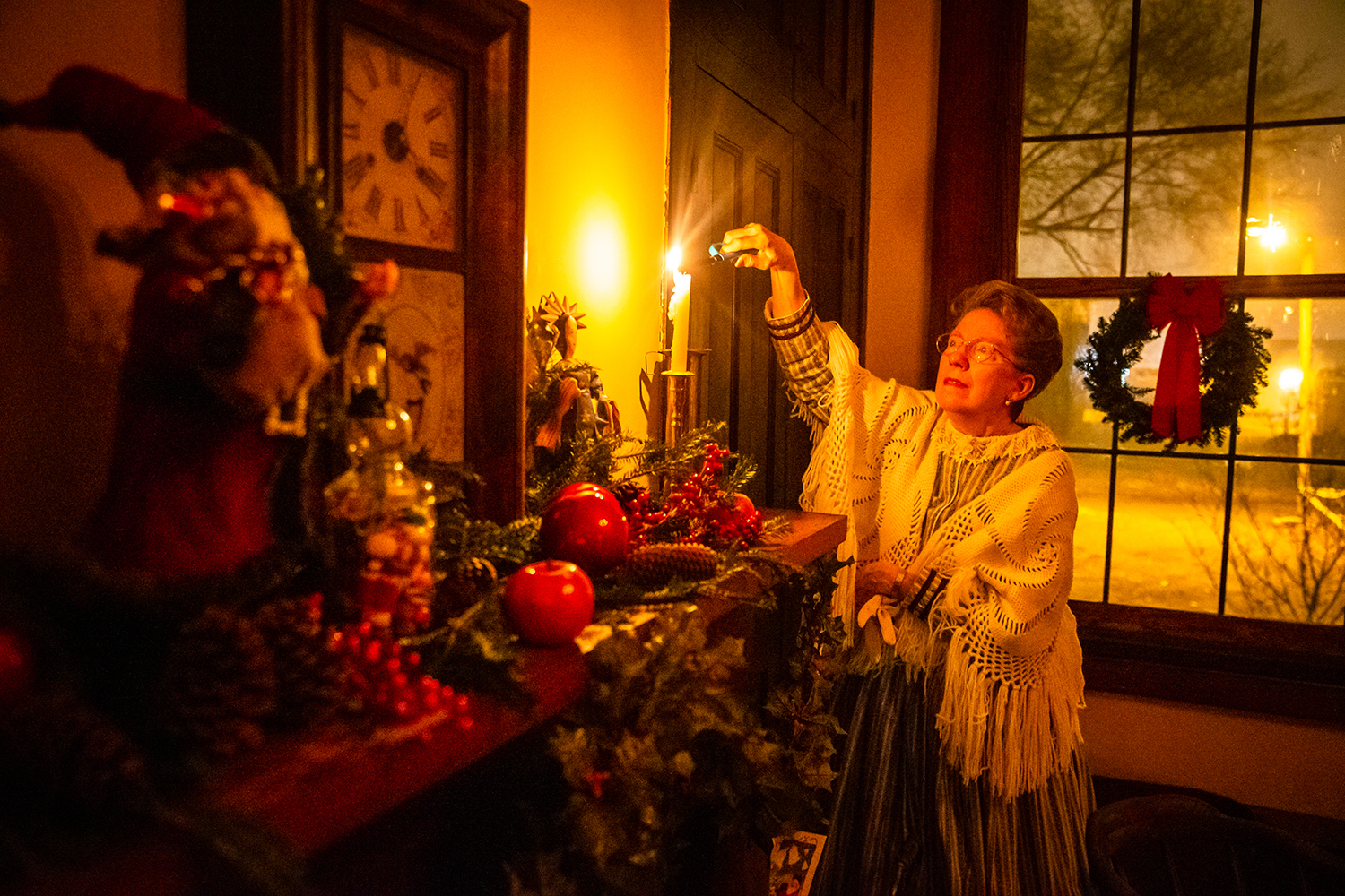 Betty Ann Poage, a volunteer with the Elijah Iles House, lights candles dressed in period clothing from the 1850s for her presenter role in one of the four rooms, each with Christmas decorations representing a time period of the 19th century, in preparation for the Iles House Candlelight Tour at the Elijah Iles House, Friday, Dec. 14, 2018, in Springfield, Ill. The house's decorated interior demonstrated how Christmas was celebrated in the 19th century and how it evolved from a relatively minor holiday into a major American celebration. The Christmas theme continues on Saturday with the Historic Christmas Open House at the Elijah Iles House featuring the decorations from 1 p.m. to 4 p.m. with children's activities, caroling and live music. [Justin L. Fowler/The State Journal-Register]