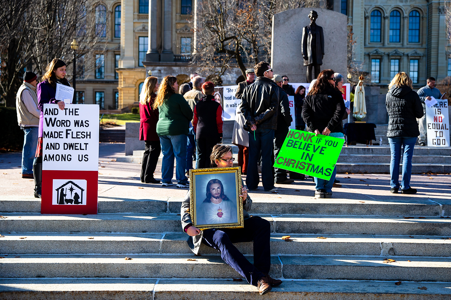 "Troy Mathews clutches his rosary in his hand as he holds a portrait of Jesus for people driving by to see as he joins a group praying the rosary during a ""Rosary of Reparation,"" in protest to the display from The Satanic Temple-Chicago in the Statehouse rotunda, in front of the Lincoln statue at the Illinois State Capitol, Sunday, Dec. 16, 2018, in Springfield, Ill. ""I needed to come here because of the life that we have and the goodness in the world,"" said Mathews. ""Evil is something we should fight to overcome and that's why I'm here."" [Justin L. Fowler/The State Journal-Register]"