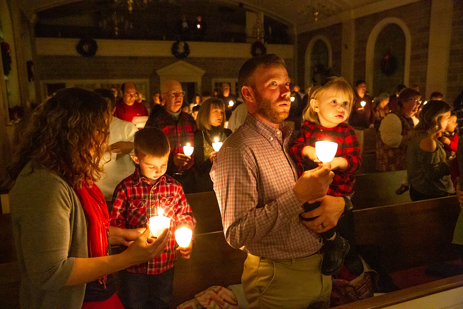 Michelle and Lee Curby and their son, Carter, 4, and daughter Claire, 1, join the congregation in singing Silent Night during the Christmas Eve candlelight service at First Congregational Church Monday, Dec. 24, 2018 in Springfield, Ill. Christians around the world celebrate the birth of Jesus on Christmas. [Rich Saal/The State Journal-Register]