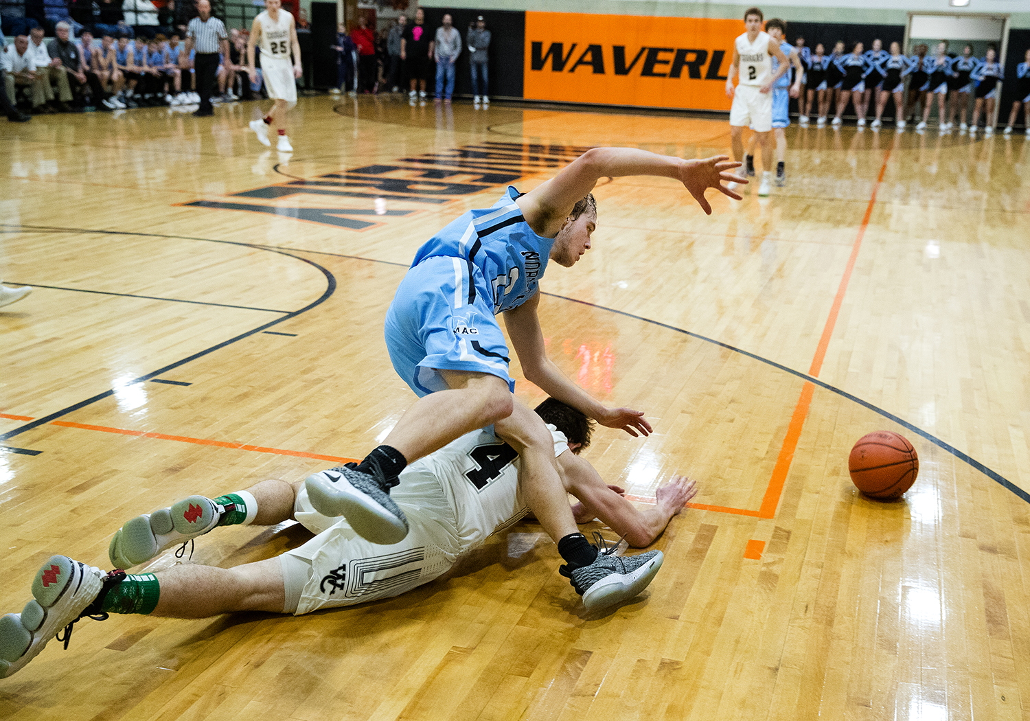 North Mac's Cole Etter trips over West Central's Ryan Moore as he lunges for a loose ball during the Waverly Holiday Tournament Friday, Dec. 28, 2018. [Ted Schurter/The State Journal-Register]