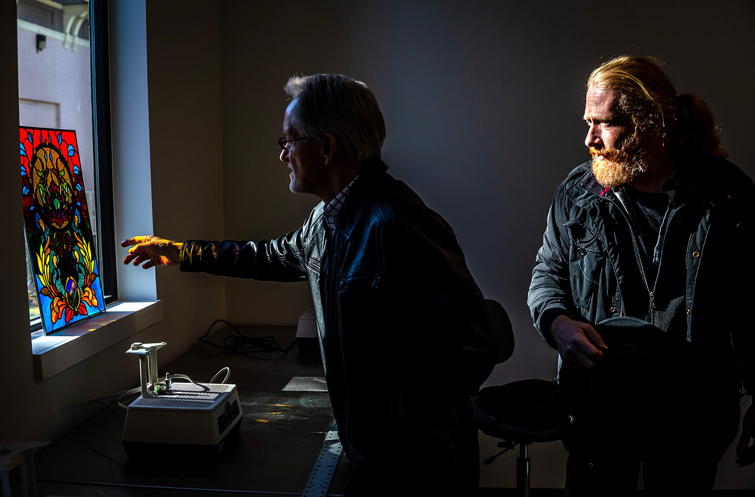 Artist Justin Behnke, right, talks with his father, Lee Behnke, as the sun lights up a late victorian style of stained glass art he made on display in the new Baima Glass Studio inside the Springfield Art Association's new studio building at 815 North 5th Street during an open house after a ribbon cutting for the new facility, Saturday, Jan. 5, 2019, in Springfield, Ill. Justin Behnke will be teaching stained glass classes in the new studio space. [Justin L. Fowler/The State Journal-Register]