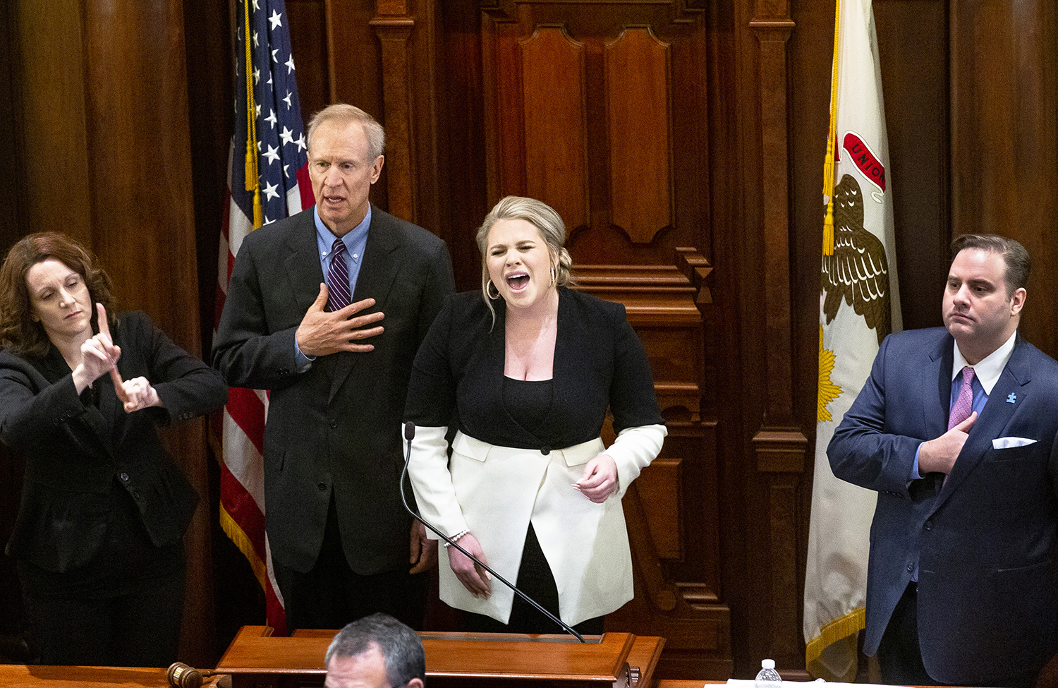 Chel Sgro, with Gov. Bruce Rauner and Senate Parliamentarian Giovanni Randazzo, right, sings the national anthem before the inauguration of the Illinois State Senate of the 101st General Assembly Wednesday, Jan. 9, 2019 at the Capitol in Springfield, Ill. Christine Lansaw, left, interprets in sign language. [Rich Saal/The State Journal-Register]