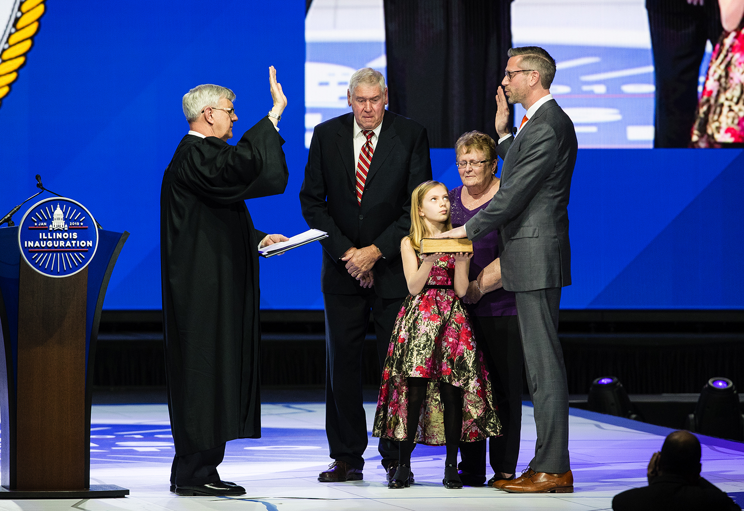 Ella Frerichs glances up at her dad, Illinois Treasurer-elect Mike Frerichs, as she holds up the Bible while he takes the oath of office from Judge Michael McCuskey during the Illinois Inaugural Ceremony at the Bank of Springfield Center Monday, Jan. 14, 2019. [Ted Schurter/The State Journal-Register]