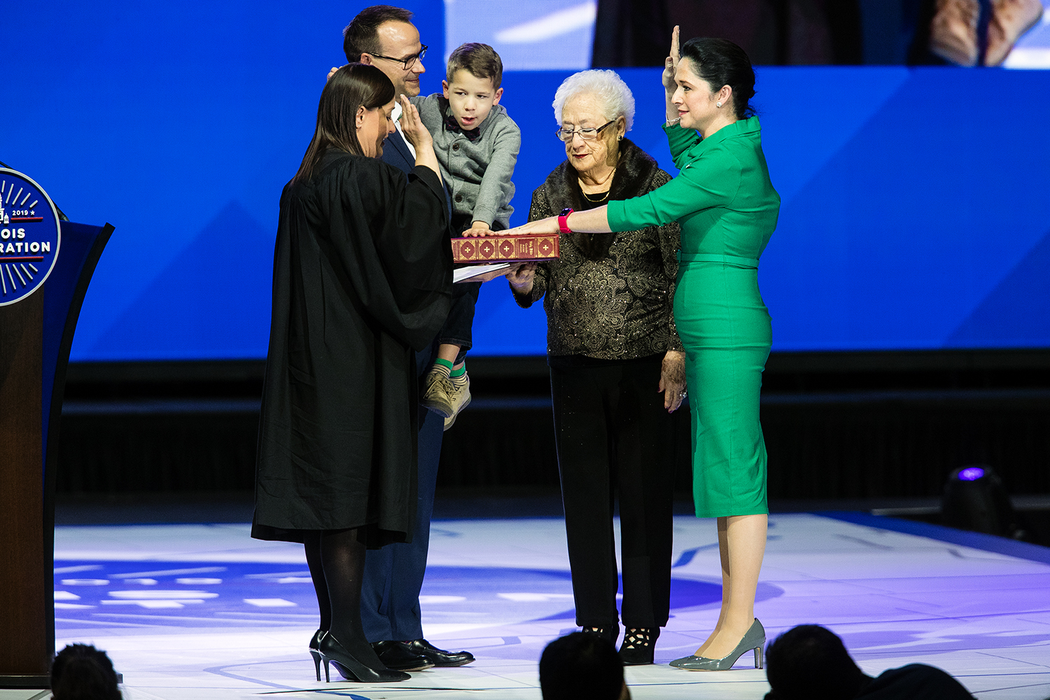 Comptroller Susana Mendoza takes the oath of office from judge Rossana Patricia Fernandez during the Illinois Inaugural Ceremony at the Bank of Springfield Center Monday, Jan. 14, 2019. Mendoza's husband, David Szostak holds their son David while her mother, Susana H. Mendoza, helps hold the Bible. [Ted Schurter/The State Journal-Register]