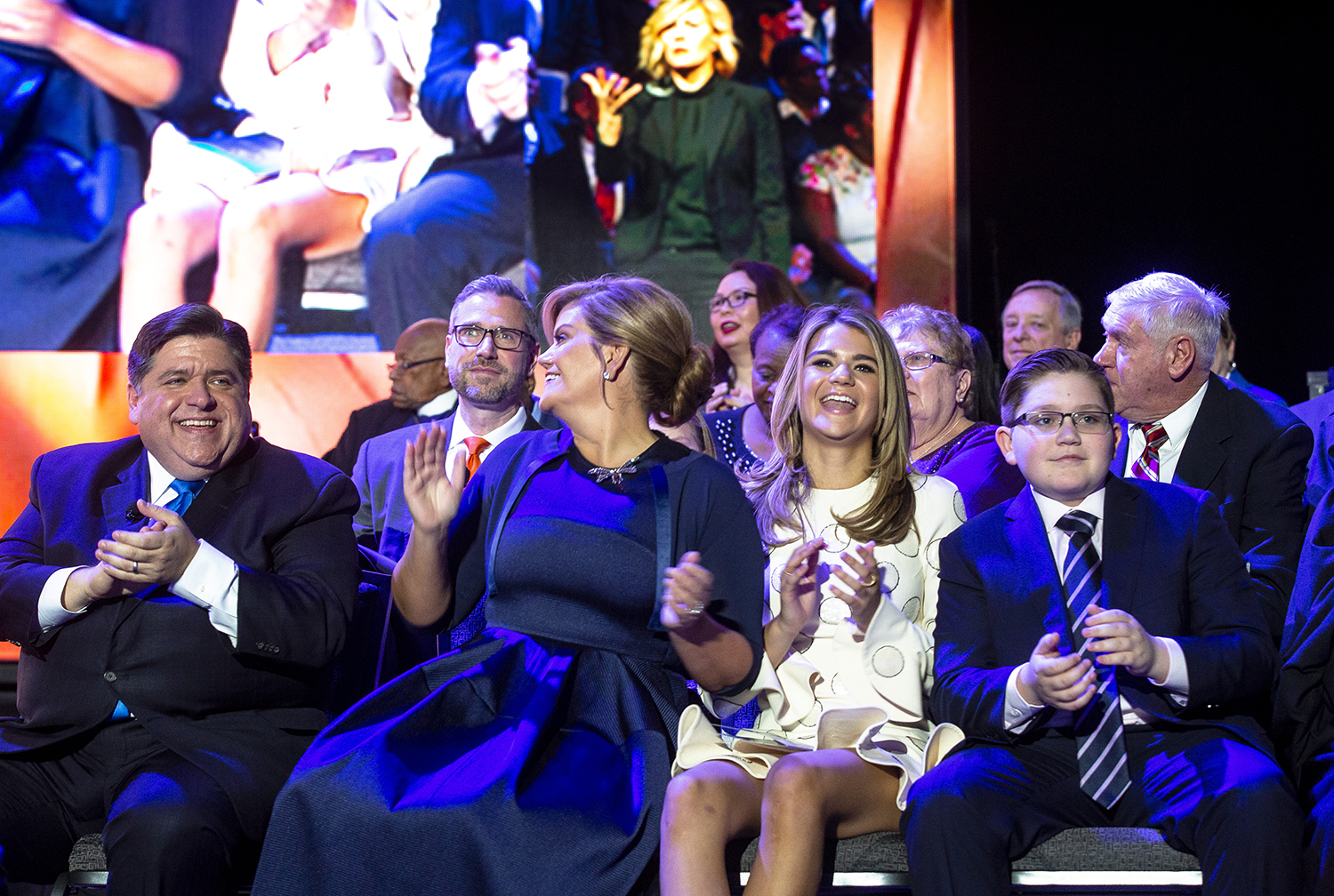 """The Pritzker family, Gov.-elect J.B., his wife M.K. and their children, Teddi and Donny, join in on a performance of """"We Are Family"""" by Soul Children of Chicago during the Illinois Inaugural Ceremony Monday, Jan. 14, 2019 a the Bank of Springfield Center in Springfield, Ill. [Rich Saal/The State Journal-Register]"""